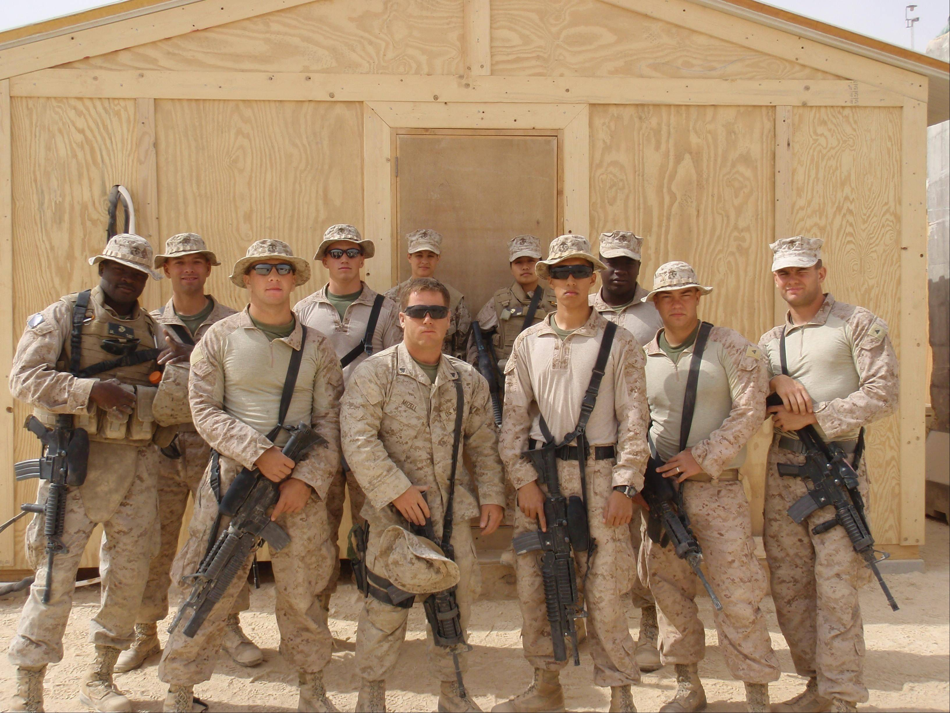 Hoffman Estates native Justin Sher, third from left, and his fellow Marines stand in front of a wooden structure (or SWA Hut) they built outside Haditha, Iraq. The care packages from the Palatine-based Yellow Ribbon Support Group kept the group going in the remote areas of their missions.