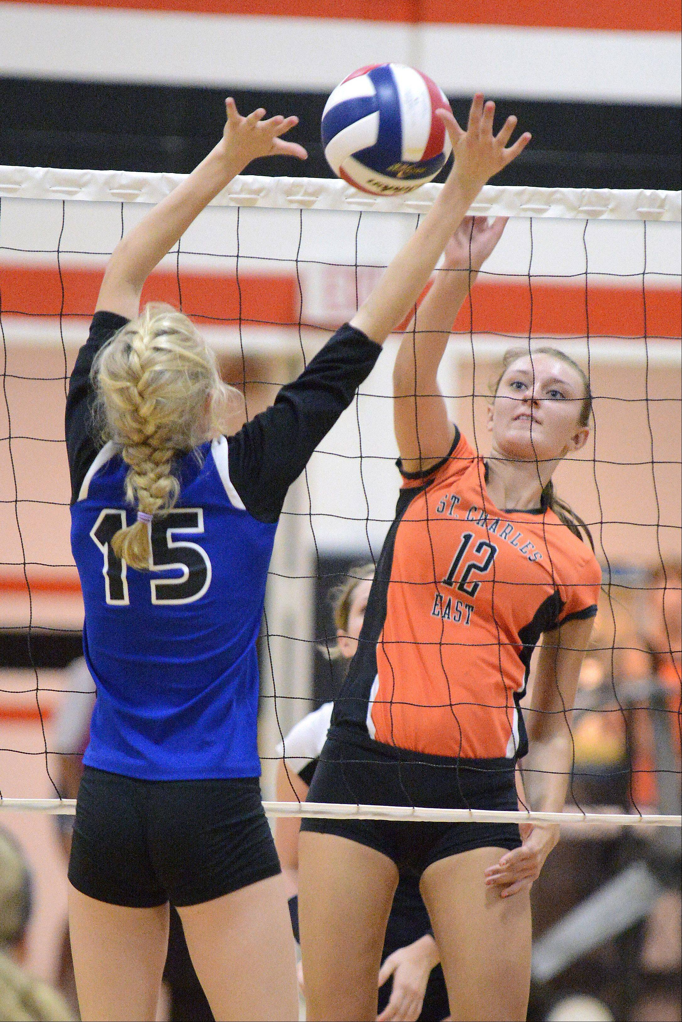 St. Charles East's Ashley Bullock spikes the ball over to Rosary's Erin Burke in the second game on Wednesday, September 4.