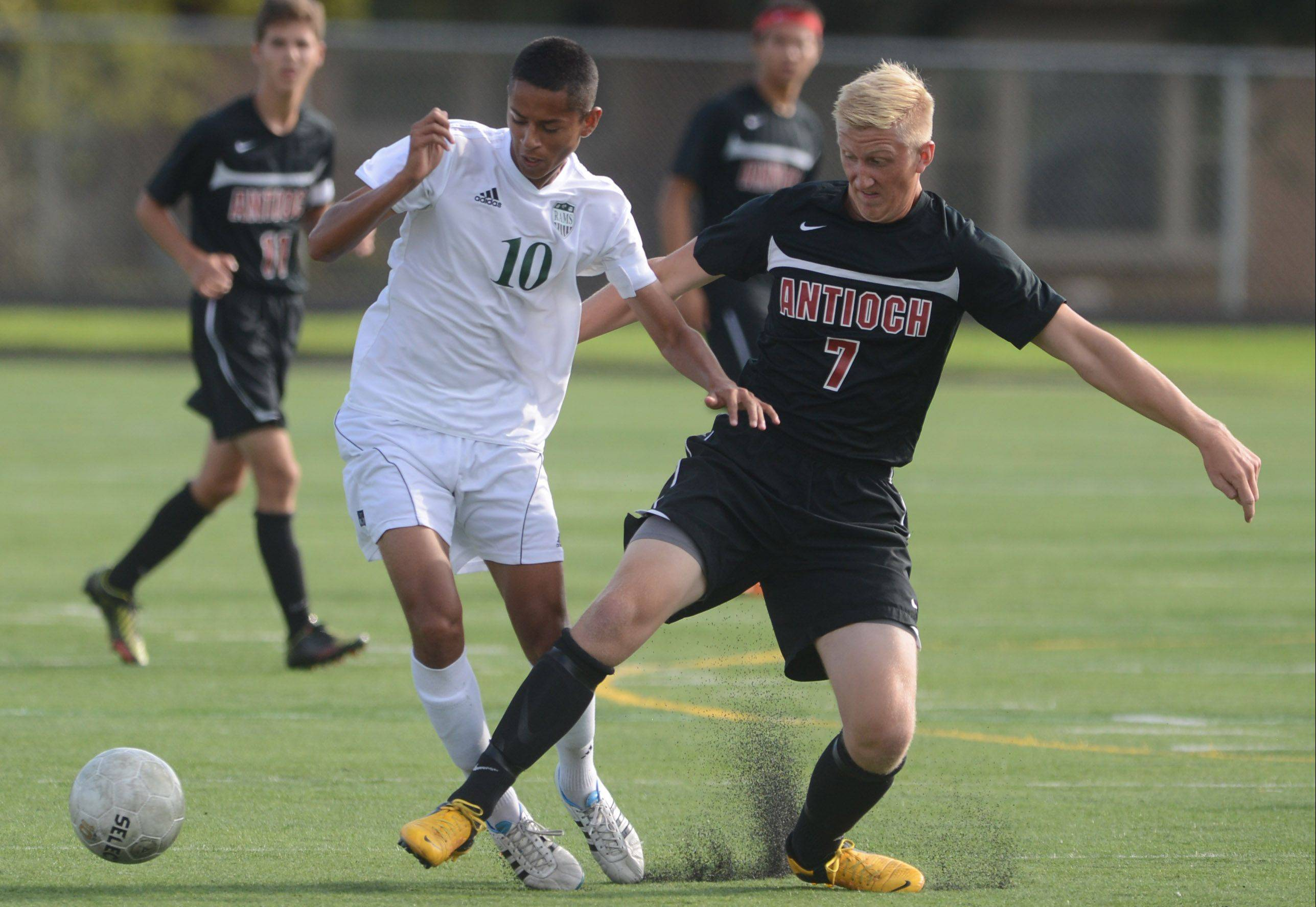 Grayslake Central's Johnny Madrid (10) fights for control with Antioch's JR Lonergan during Wednesday's soccer match in Grayslake.