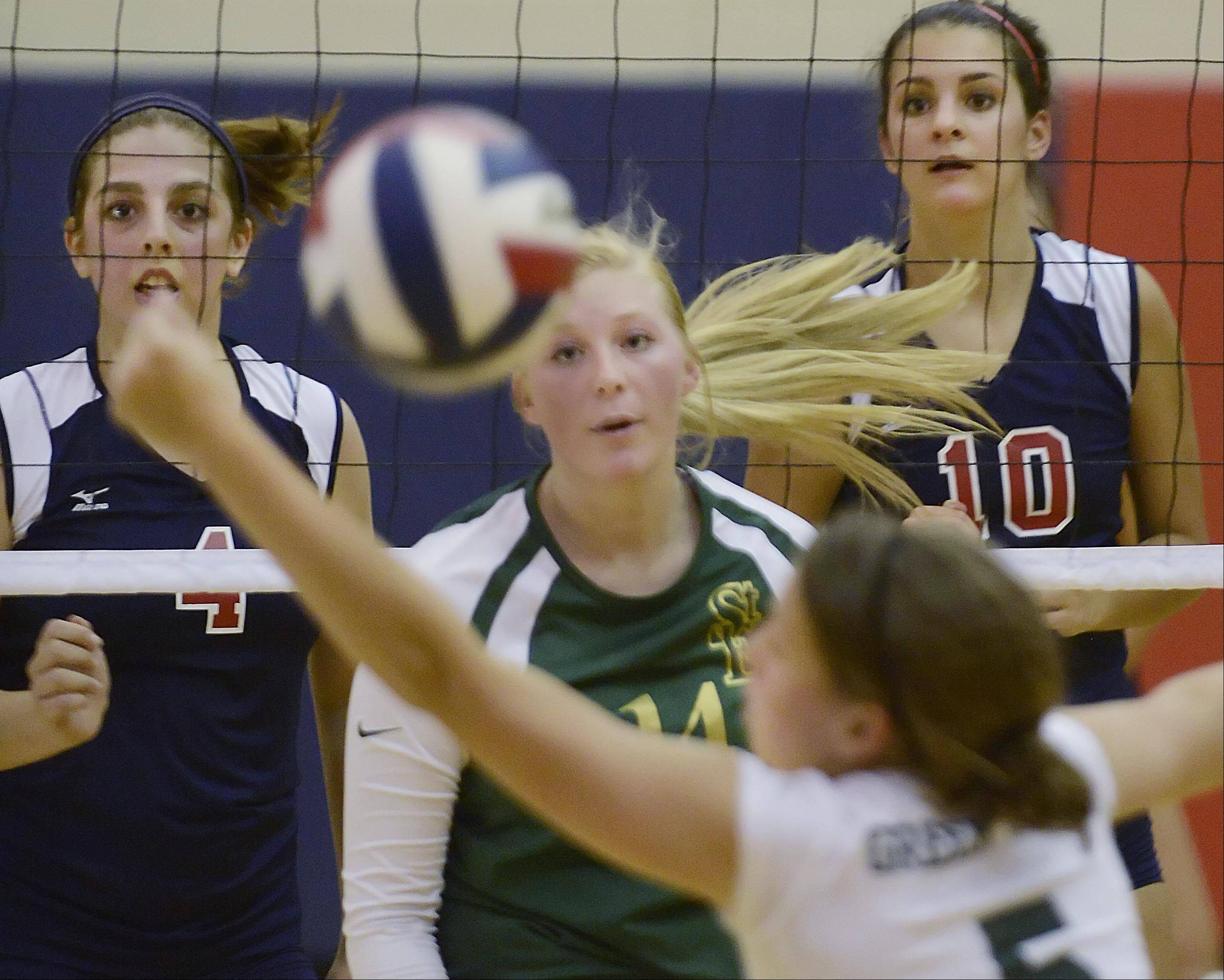 St. Edward's Allison Kruk lunges to save a shot as teammate Shannon Igielski and South Elgin's Adrianna Loiacono and Alyssa Miner watch Wednesday in South Elgin.