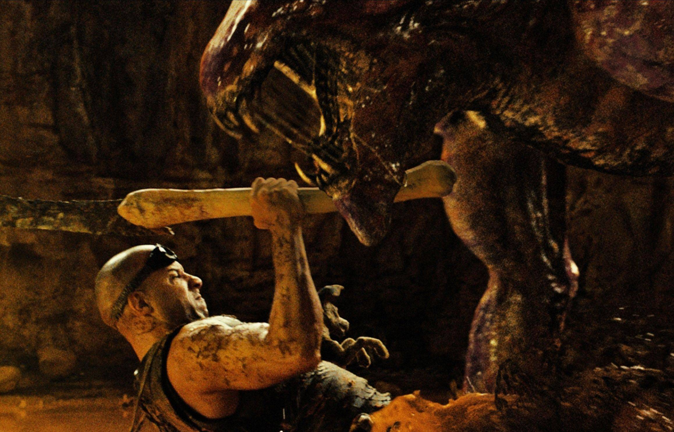 "Riddick (Vin Diesel) fends off a giant scorpion/dinosaur-like critter on a sepiatone planet in David Twohy's thriller ""Riddick."""