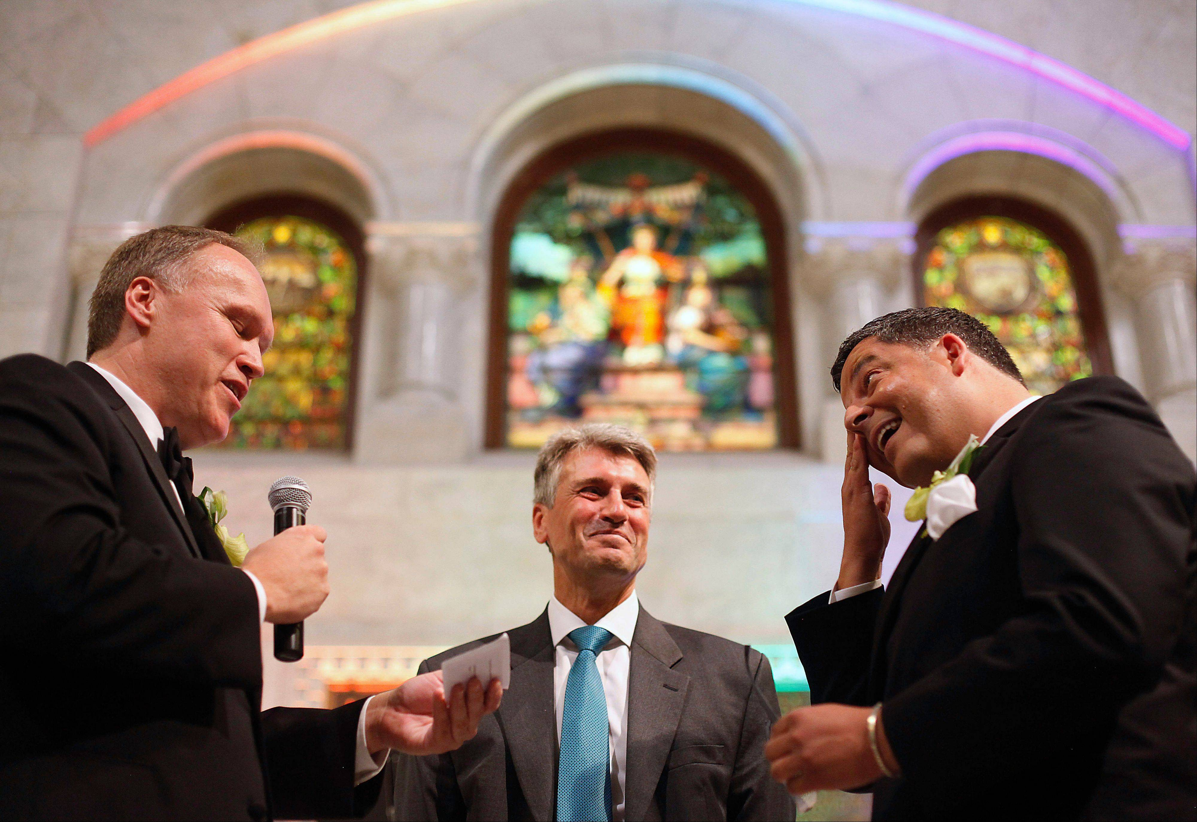 Minneapolis Mayor R.T. Rybak, center, officiates at the wedding of Al Giraud, right, and his partner, Jeff Isaacson, at the Minneapolis City Hall. They were the first gay couple legally married in Minnesota. Rybak is hitting the road to promote his state�s new gay marriage law.