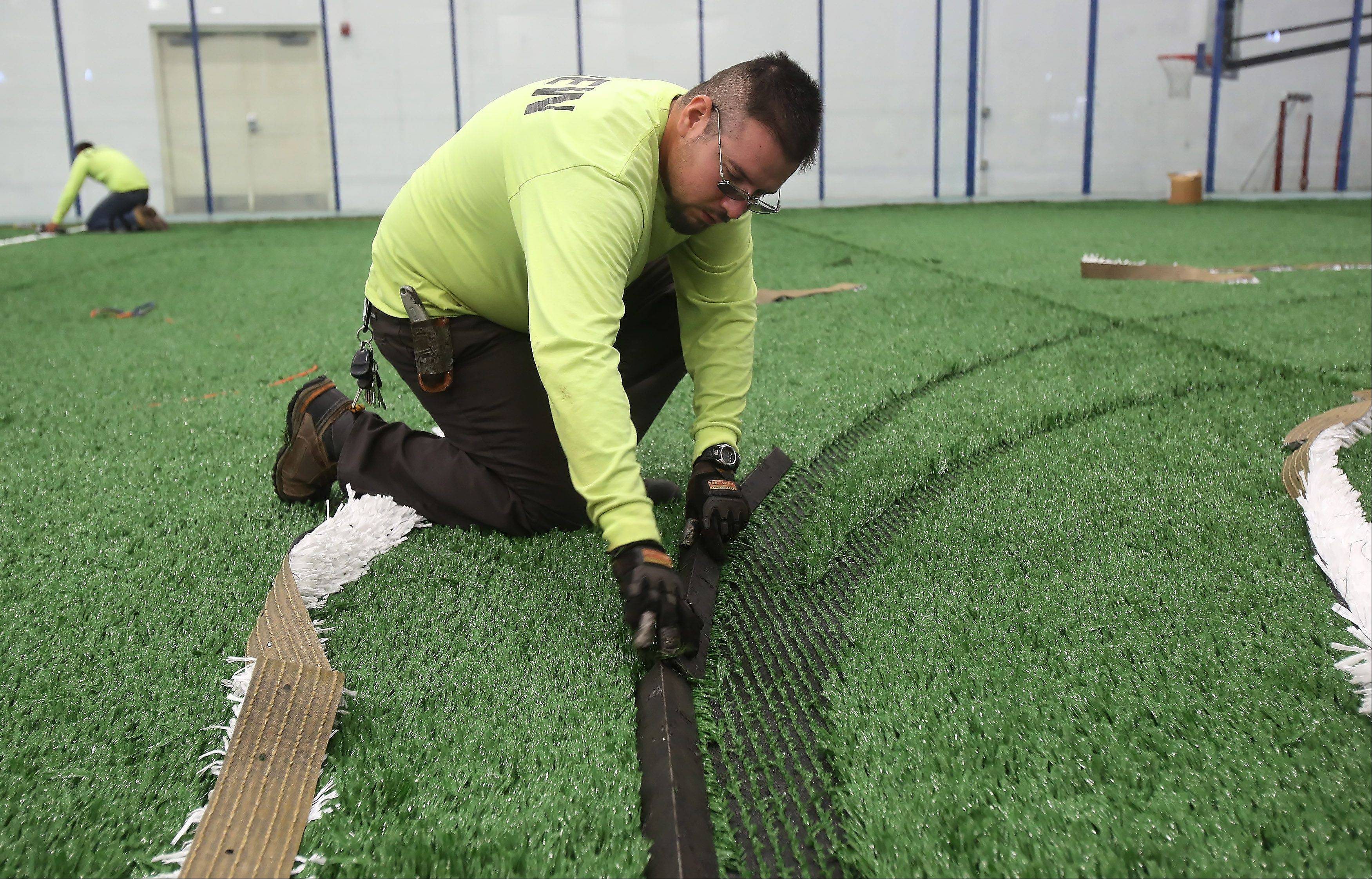 Installer Arturo Duran of FieldTurf installs the lines Wednesday for the new artificial turf on the indoor fields at the Libertyville Sports Complex.