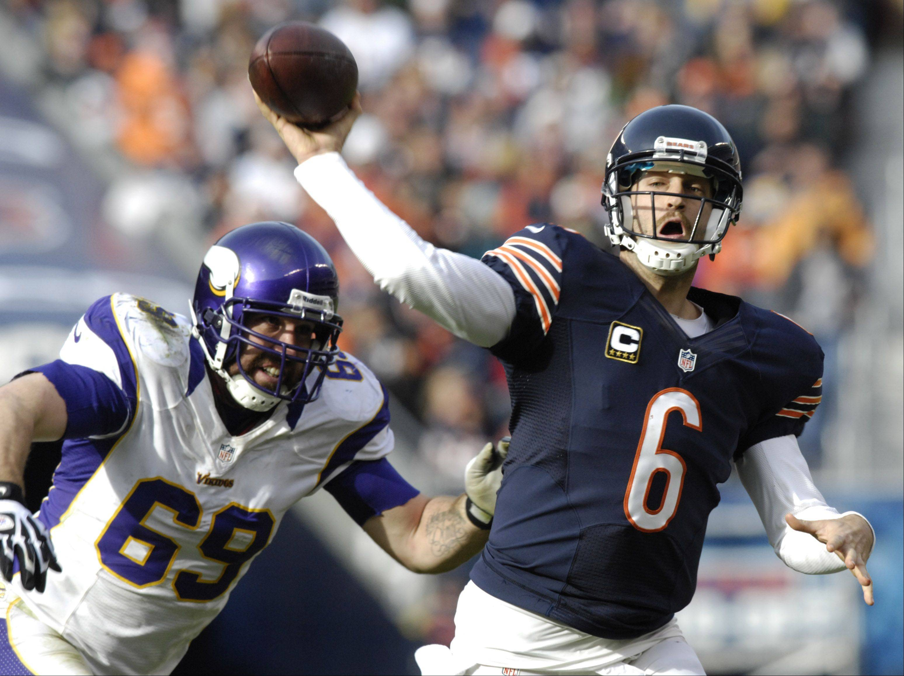 JOE LEWNARD/jlewnard@dailyherald.com � Chicago Bears quarterback Jay Cutler throws a second-quarter touchdown pass to tight end Matt Spaeth while being pursued by Minnesota Vikings defensive tackle Jared Allen at Soldier Field Sunday.