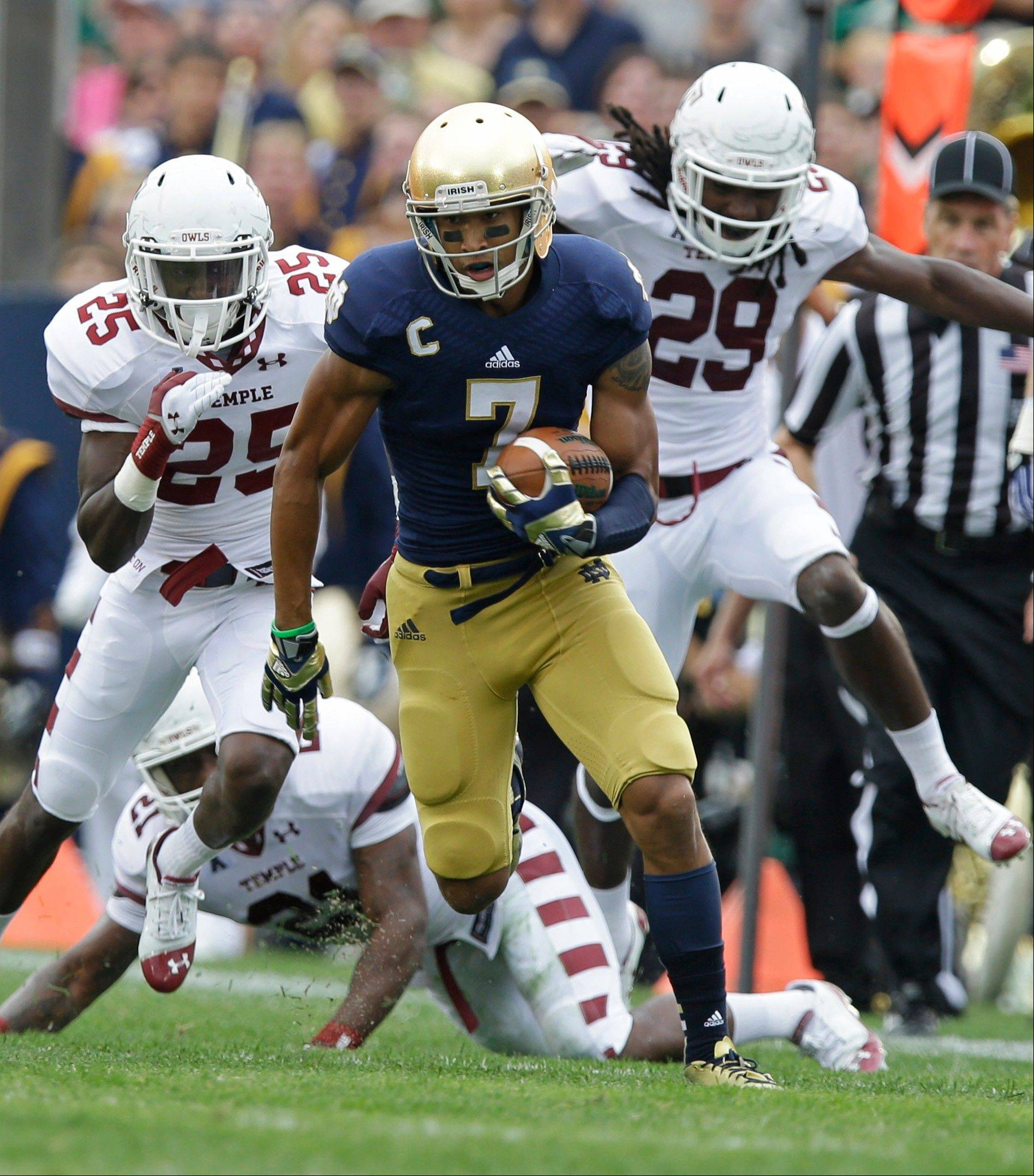 Notre Dame wide receiver TJ Jones picks up 51 yards on a catch after getting past Temple�s Tavon Young (25) and Stephaun Marshall during the first half of last Saturday�s game in South Bend, Ind.