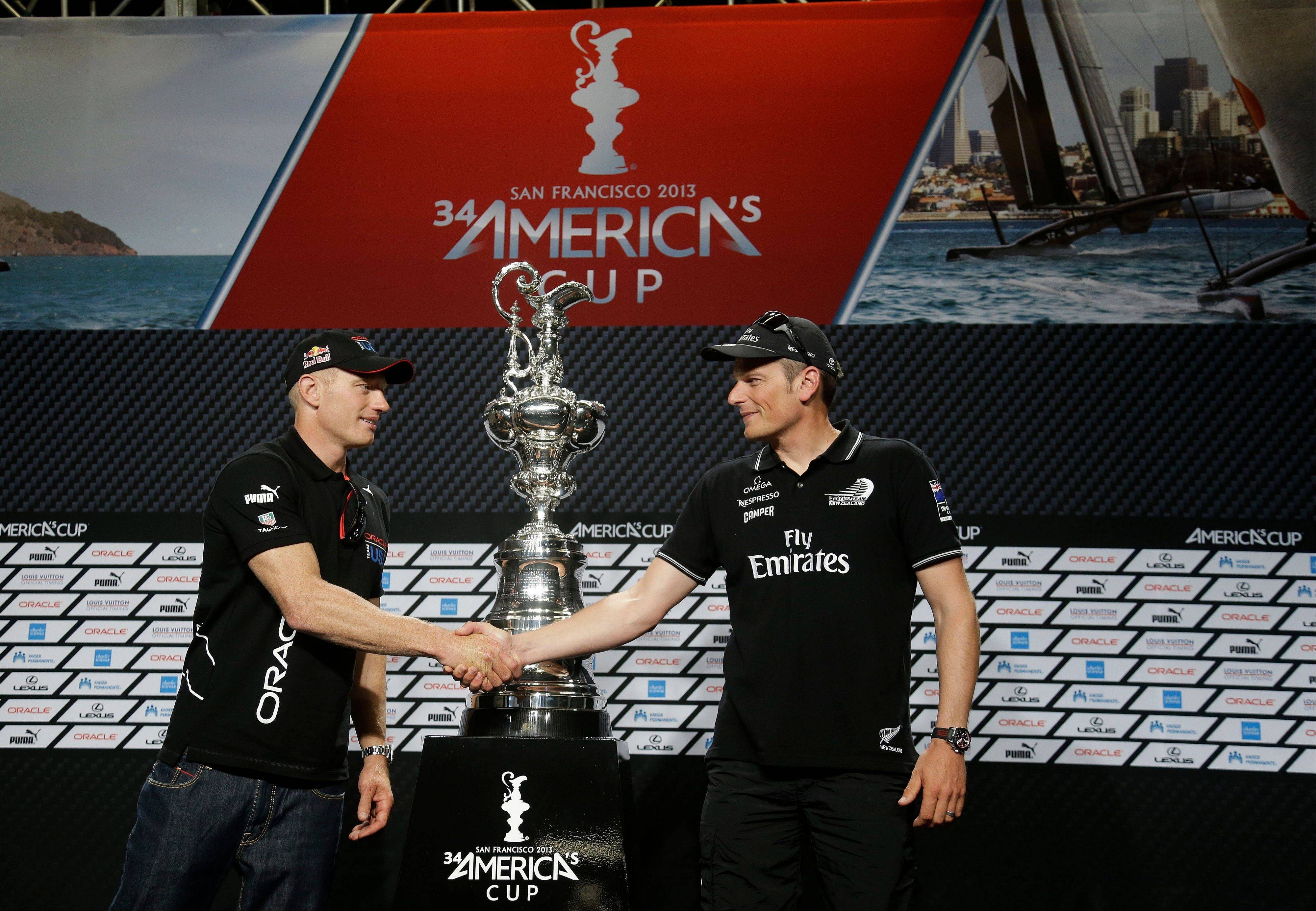 Jimmy Spithill, left, skipper of Oracle Team USA and Dean Barker, right, skipper of Emirates Team New Zealand shake hands while posing with the America's Cup trophy following a news conference Thursday, Sept. 5, 2013, in San Francisco. The first races between Oracle Team USA and Emirates Team New Zealand are on Saturday. (AP Photo/Eric Risberg)