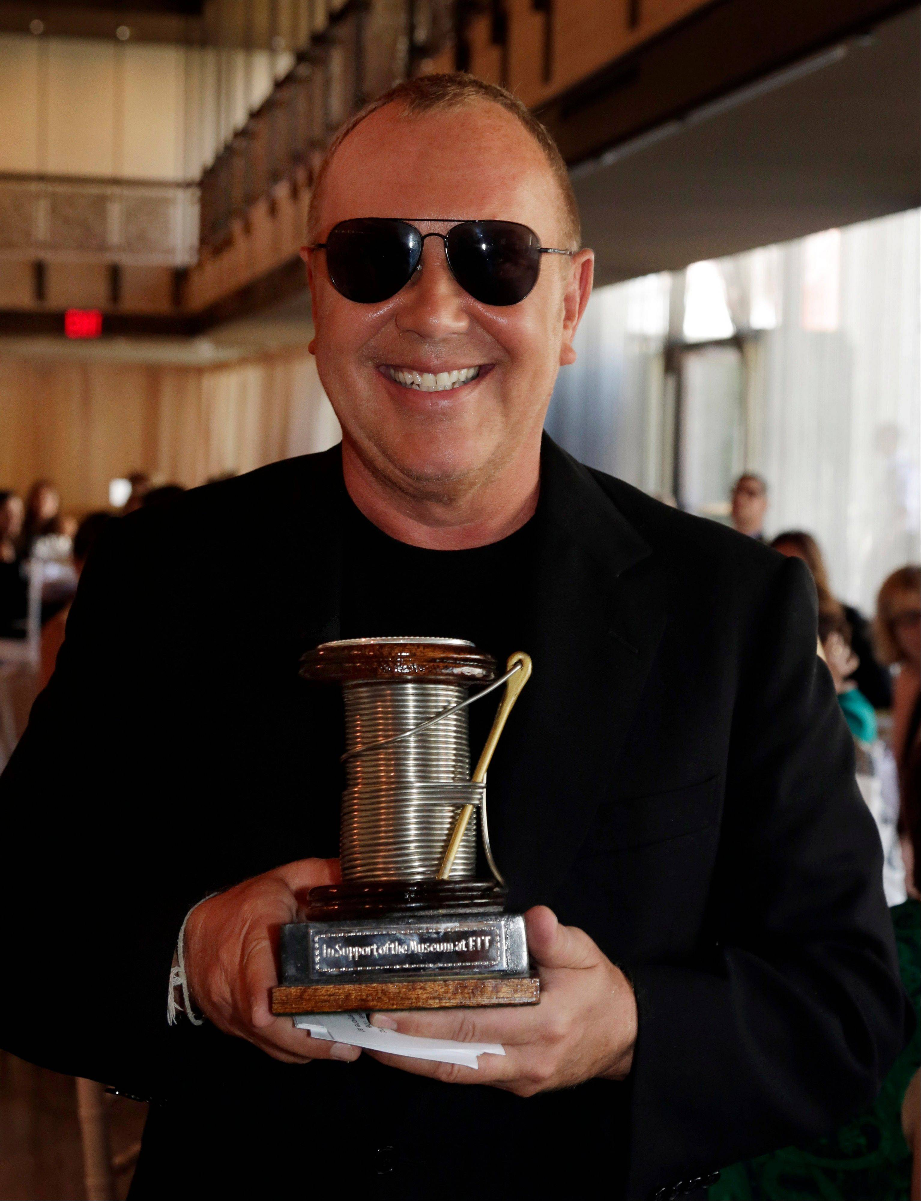 Designer Michael Kors holds the 2013 Couture Council Award for Artistry of Fashion presented by actress Hilary Swank during a luncheon in the David H. Koch Theater of New York's Lincoln Center.