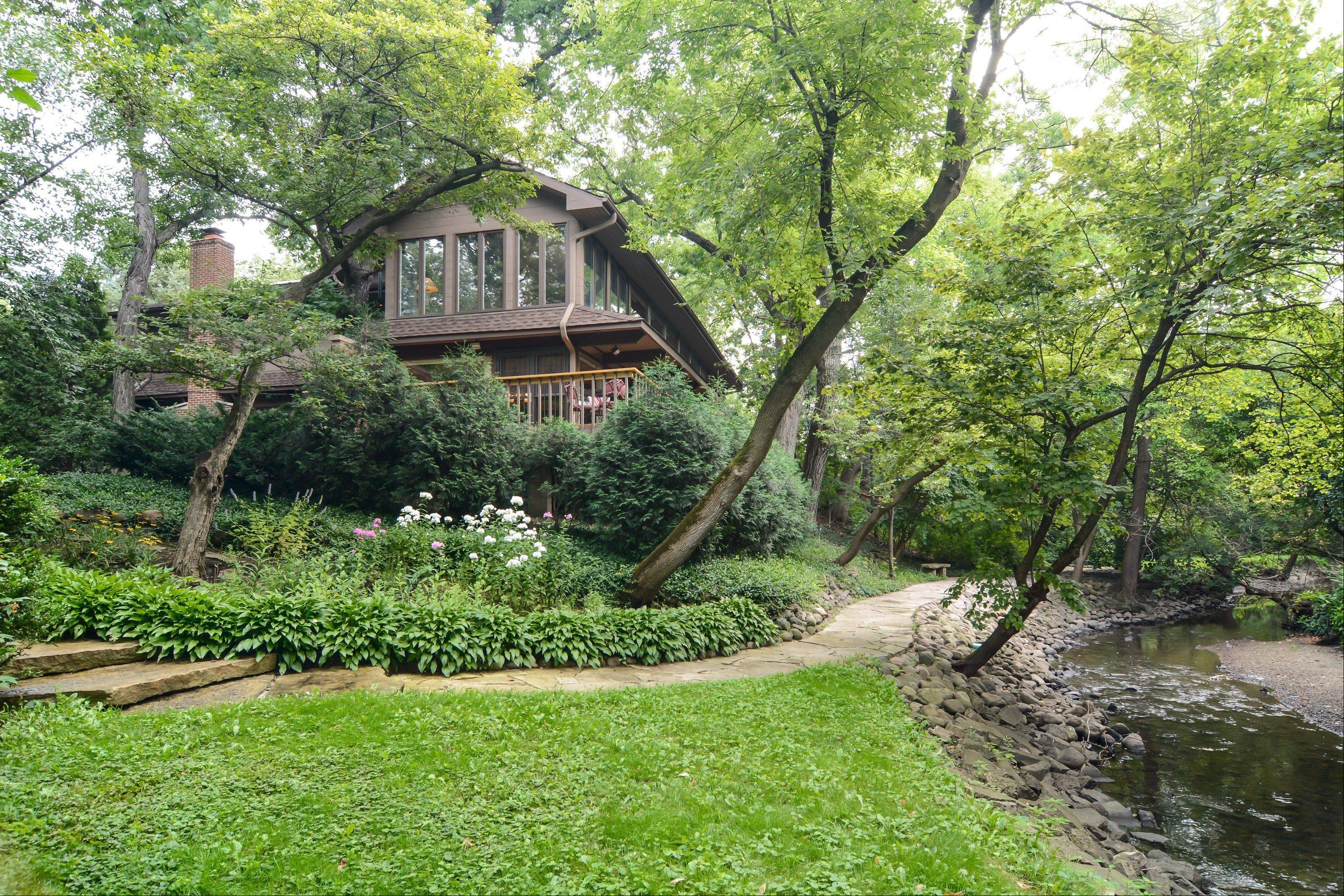 A small creek travels through the woods near this one-of-a-kind Palatine home.