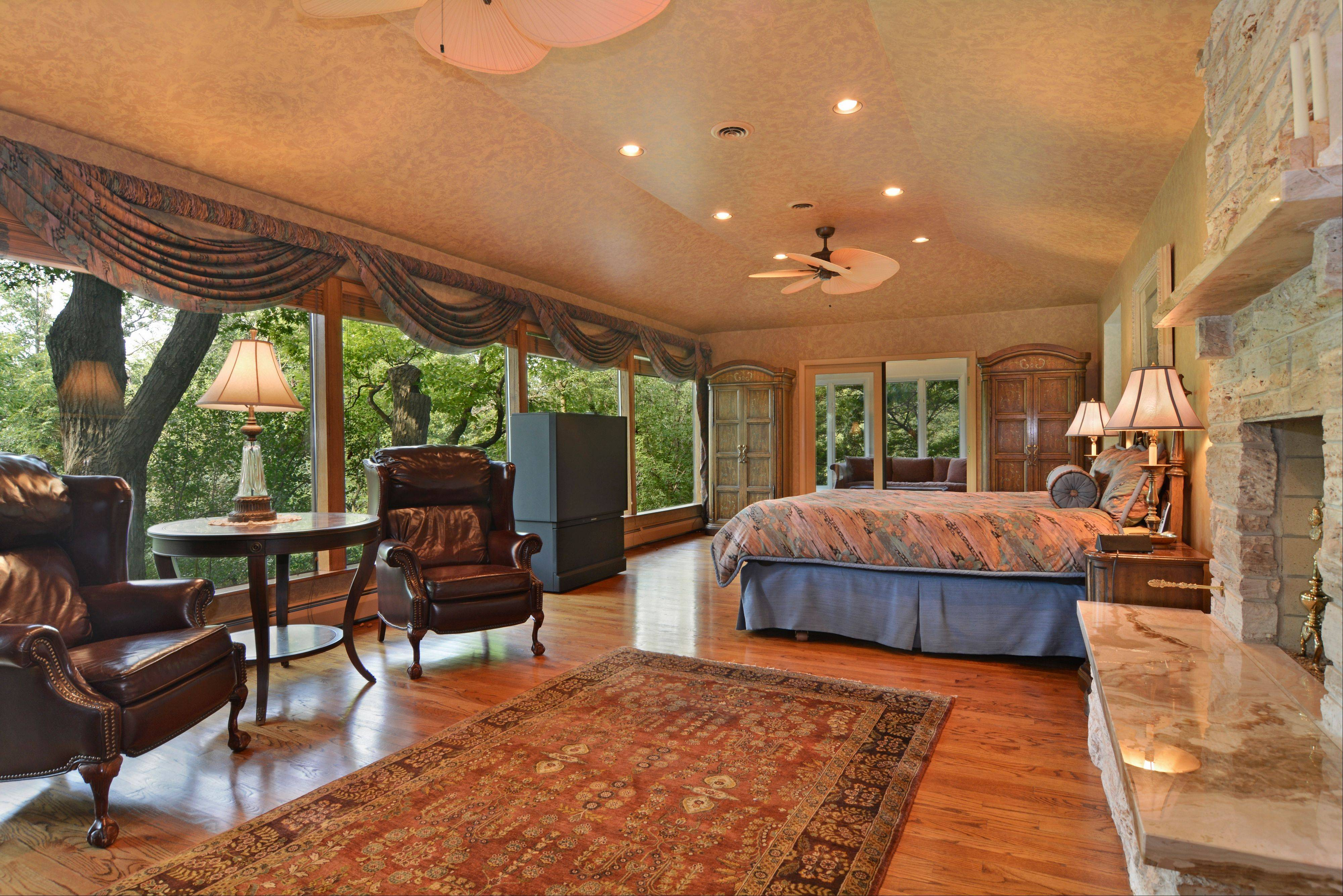 The second-floor master bedroom suite overlooks the trees with its wall of windows.
