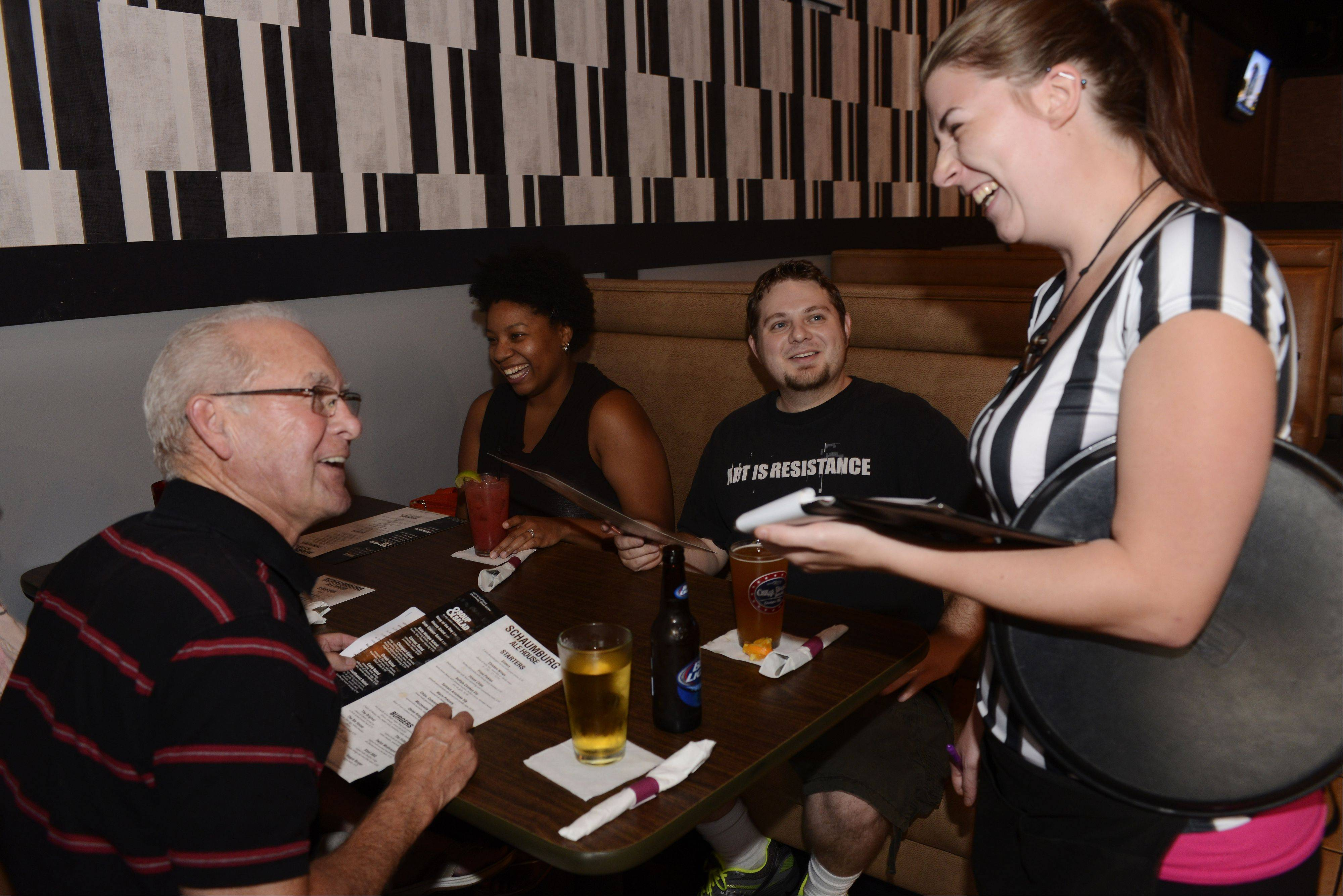 Server Traci Johnson takes an order from guests Russ Clark, left, of Peoria and Cherry and Mitch Clark of Streamwood at Schaumburg Ale House.