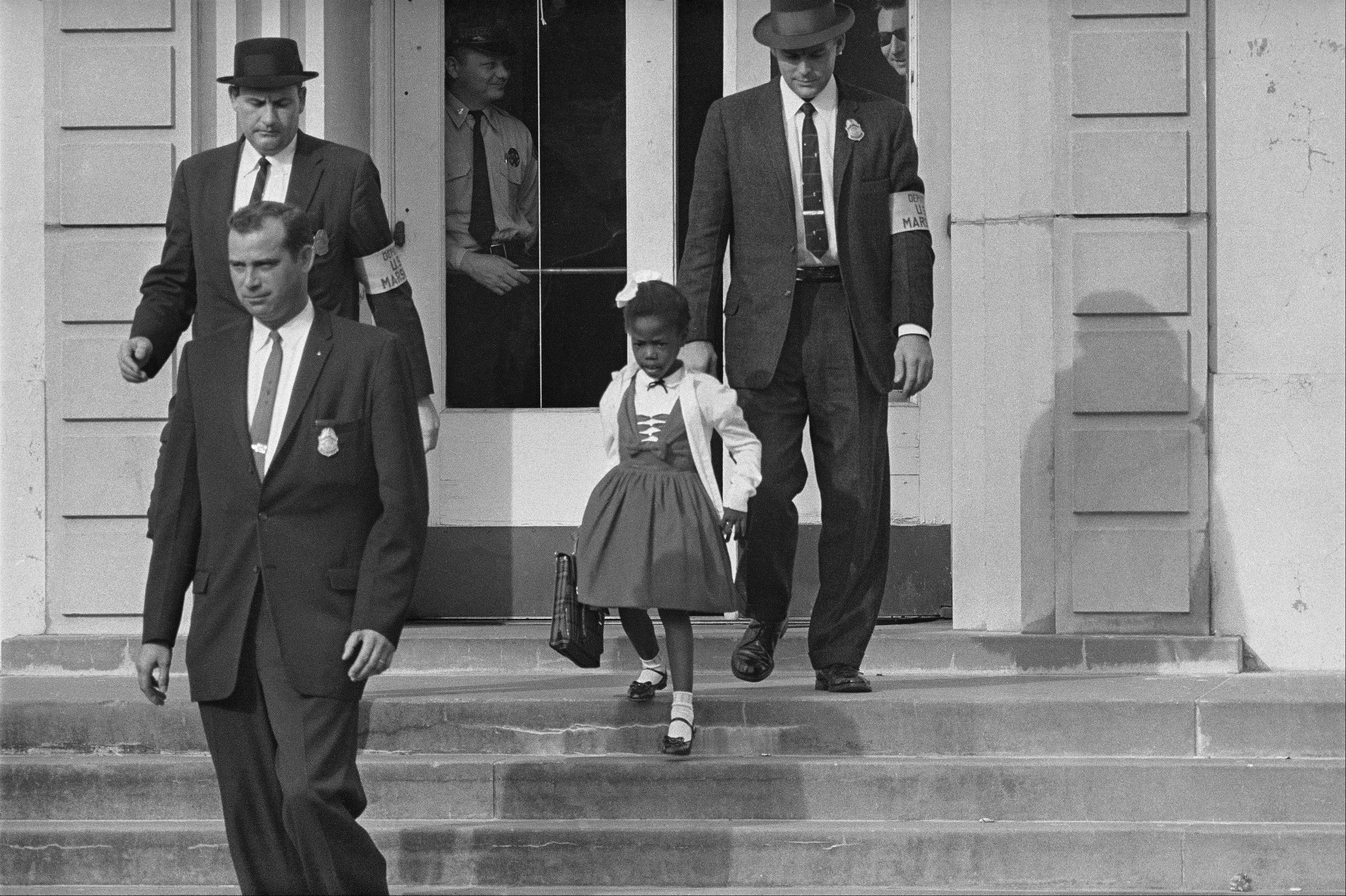U.S. Deputy Marshals, including Charles Burks, top left, escort 6-year-old Ruby Bridges from William Frantz Elementary School in New Orleans, La. The first-grader was the only black child enrolled in the school.