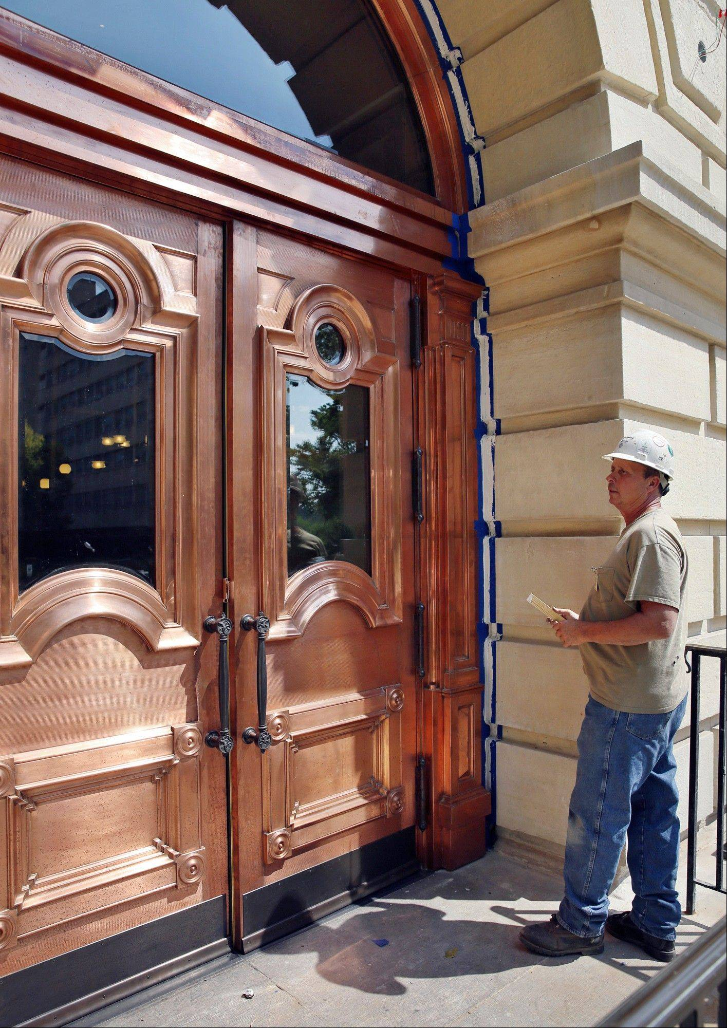 Bill Werner finishes up work on the copper-covered doors for the west entrance to the state Capitol last month in Springfield. The $50 million renovation of the building includes three sets of copper-covered wooden doorways that cost $669,608.