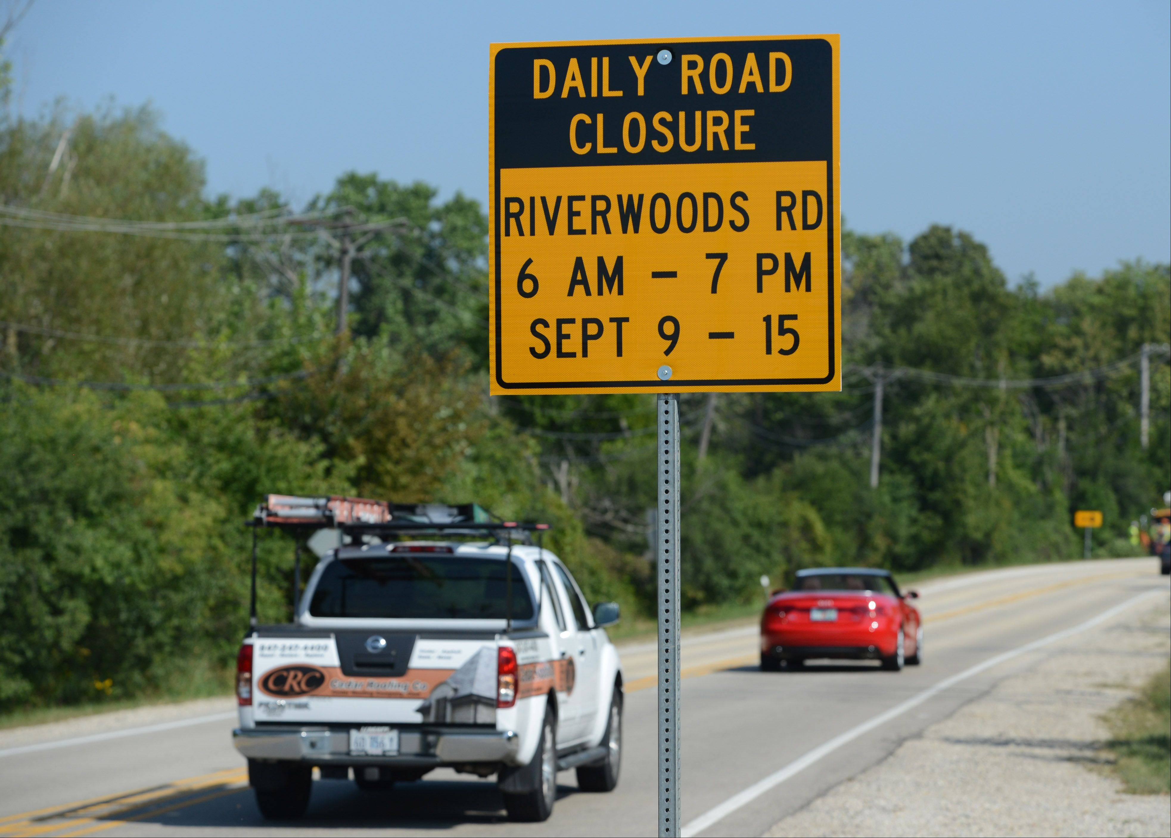 A temporary sign sits along southbound Riverwoods Road near Everett Road alerting drivers to upcoming closures due to parking on land owned by W.W. Grainger Inc. in Mettawa for the BMW Champi