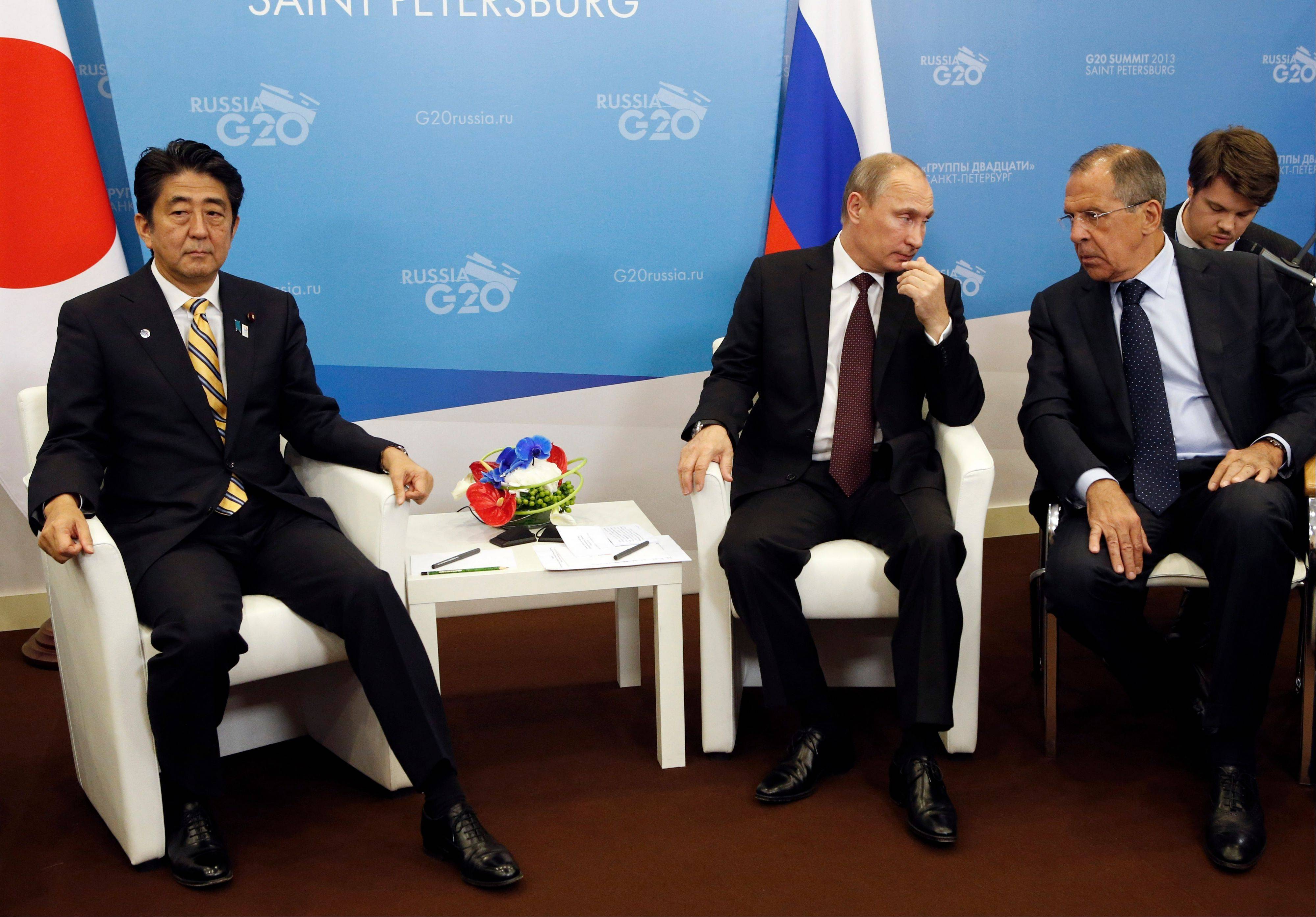 Russia's President Vladimir Putin, third from right, speaks Thursday with Russian Foreign Minister Sergey Lavrov, second from right, while meeting with Japan's Prime Minister Shinzo Abe, left, on the sidelines of a G-20 summit in St. Petersburg, Russia.