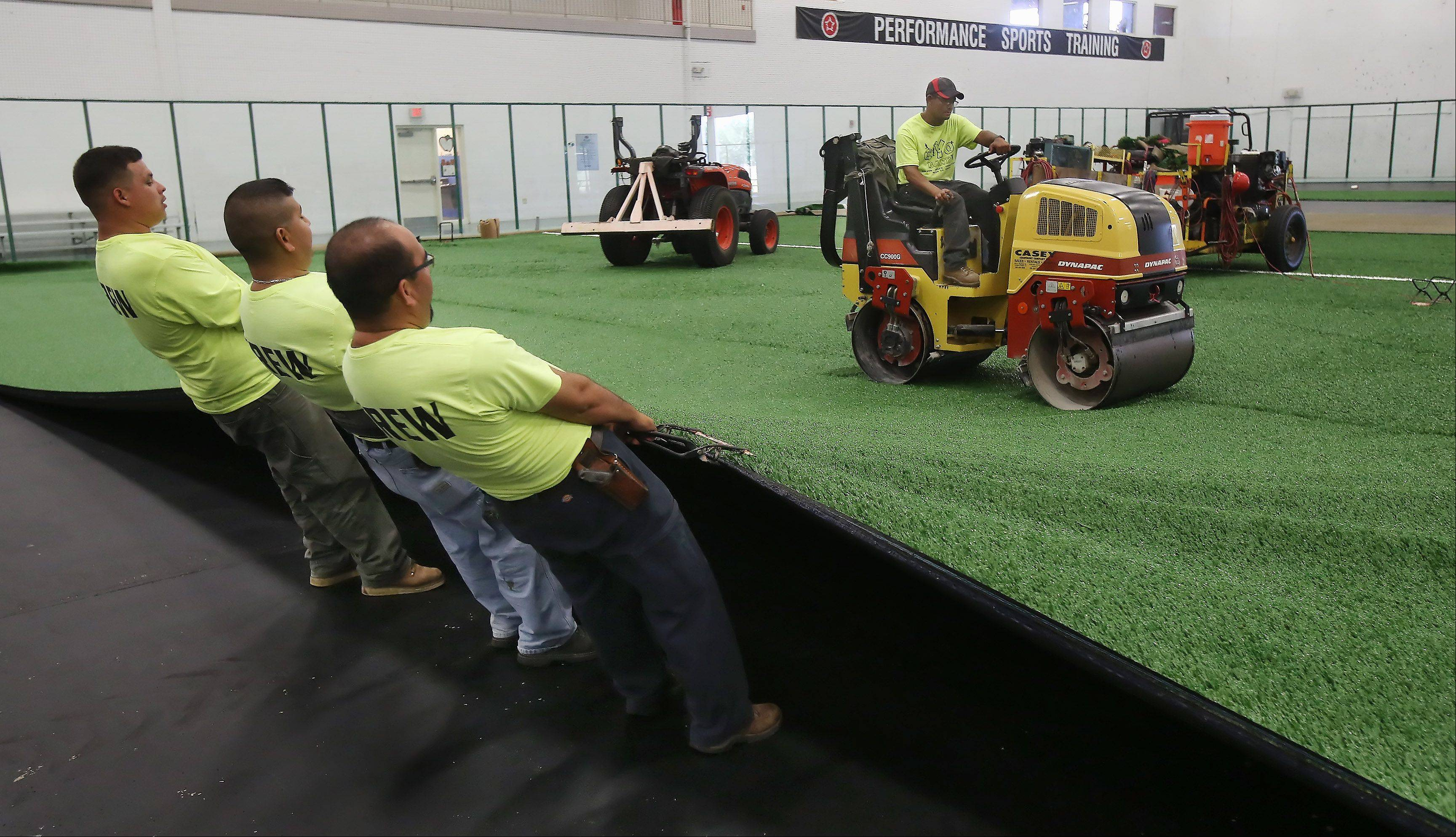 Arturo Ramirez of FieldTurf uses a roller to flatten the turf as other installers stretch it into place during the installation Wednesday of new artificial surfaces at the two indoor fields at the Libertyville Sports Complex.
