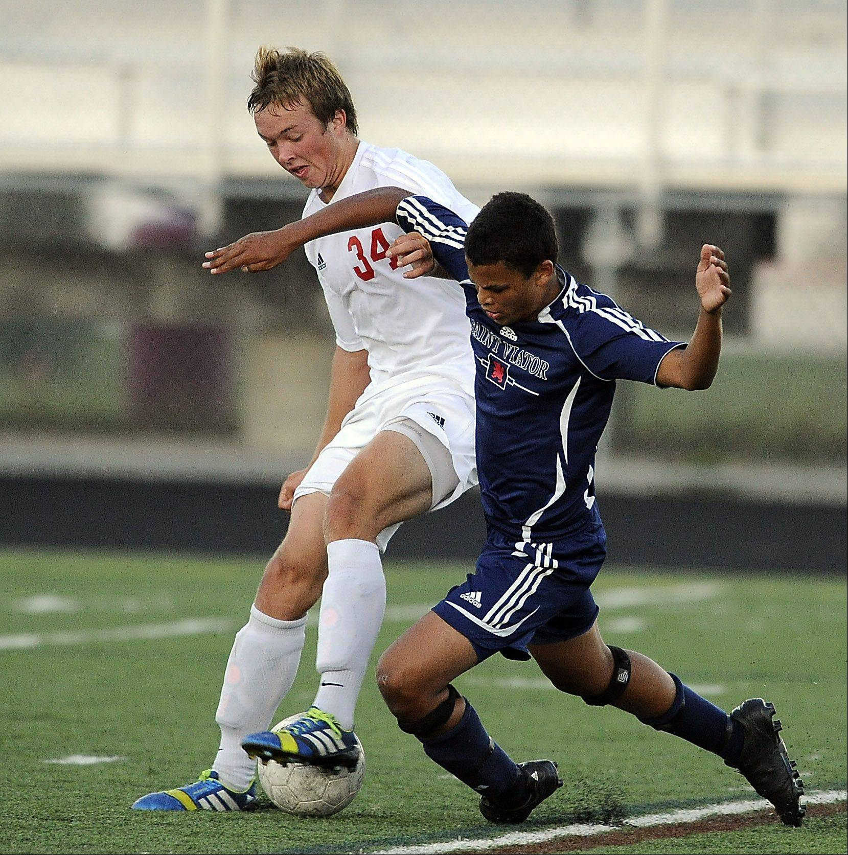 Mark Welsh/mwelsh@dailyherald.comPalatine's Gavin Falotico, left, and St. Viator's Kevin Klinkenberg battle for the ball in the first period Thursday at Palatine.