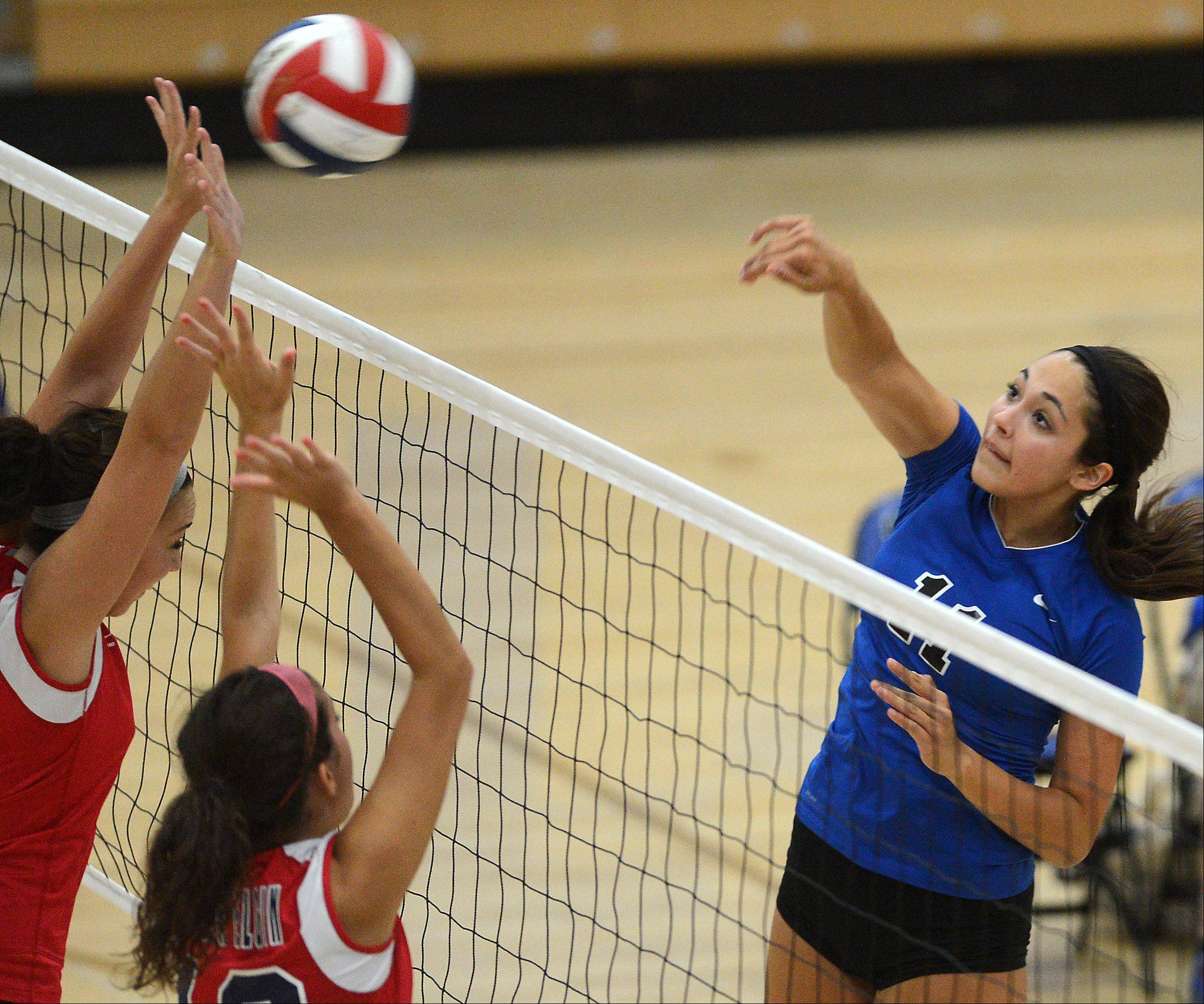 St. Charles North's Sophia DuVall records a kill as she spikes it past a pair of South Elgin blockers during Thursday's game in St. Charles.
