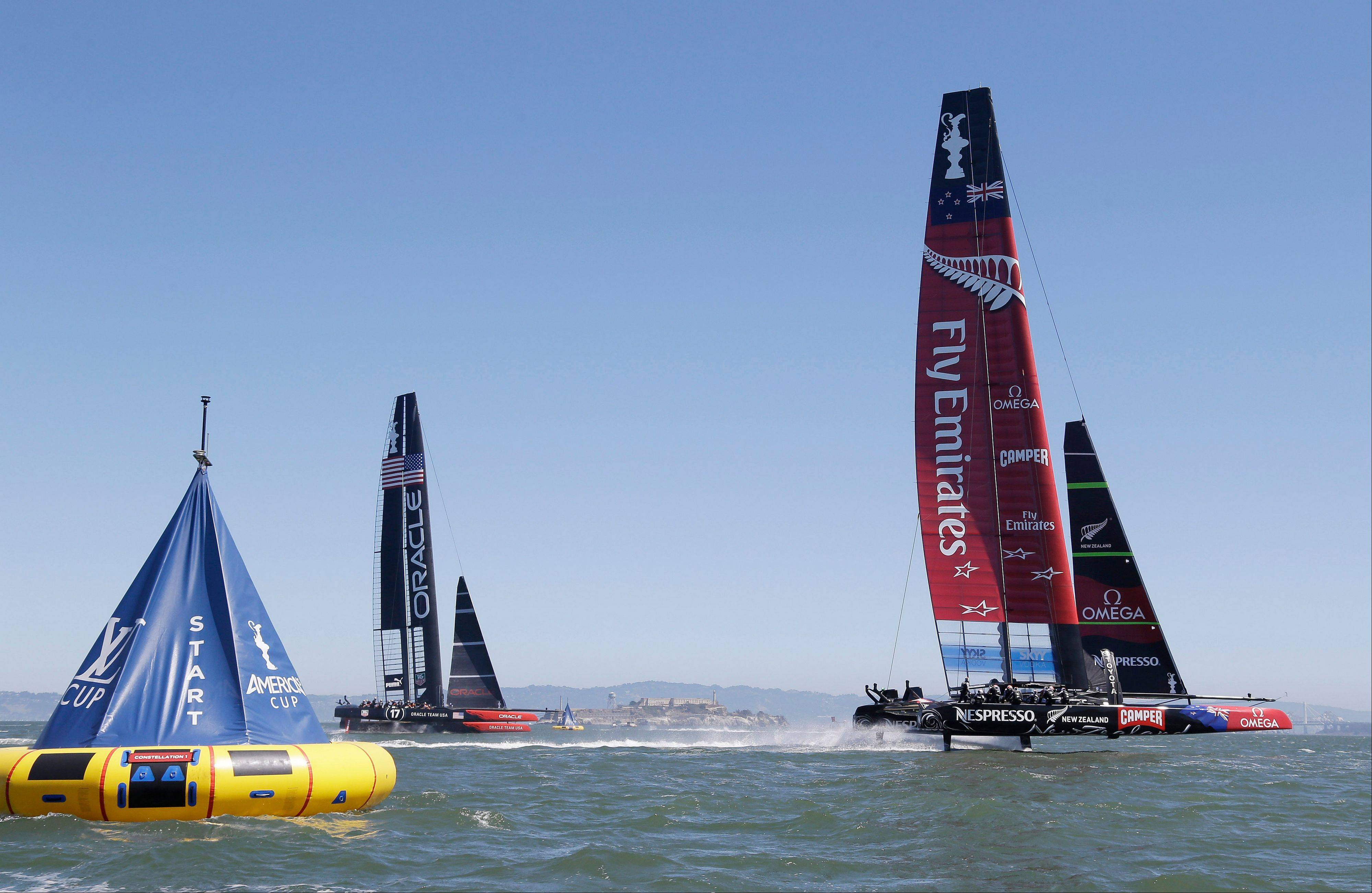 Emirates Team New Zealand, right, and Oracle Team USA, left, make their way past the start line while training for the America's Cup sailing event on Thursday, Sept. 5, 2013, in San Francisco. The first races between Oracle Team USA and Emirates Team New Zealand are on Saturday. Alcatraz Island is visible in the distance.