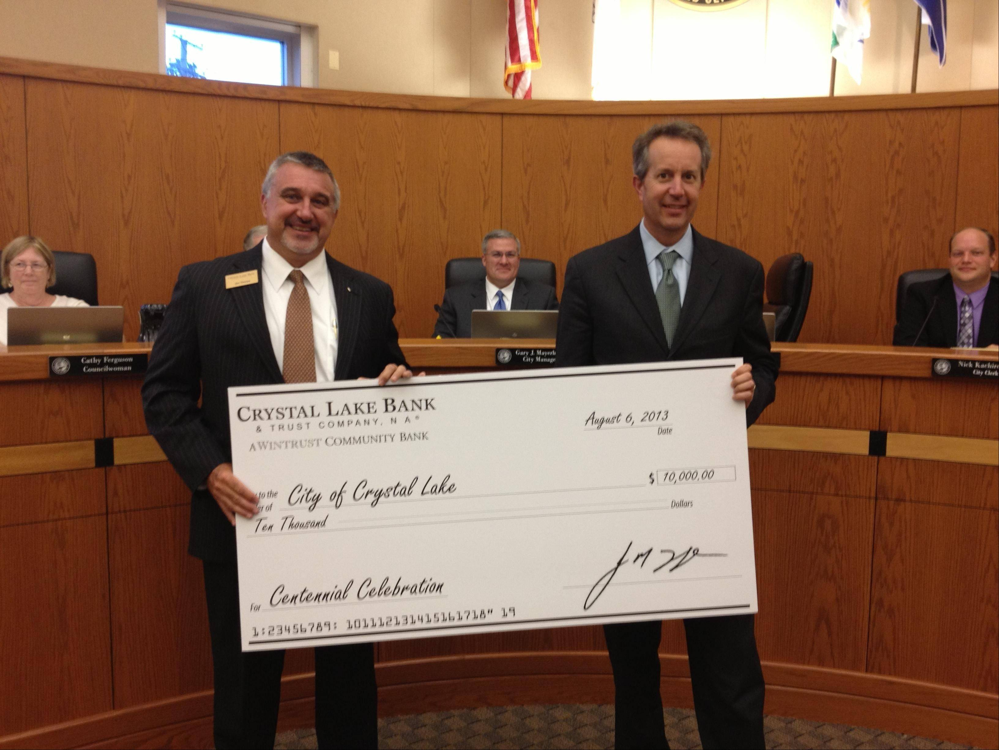 Jim Thorpe, left, president of Crystal Lake Bank & Trust, presents a $10,000 donation for the Crystal Lake's Centennial Celebration to Mayor Aaron Shepley.