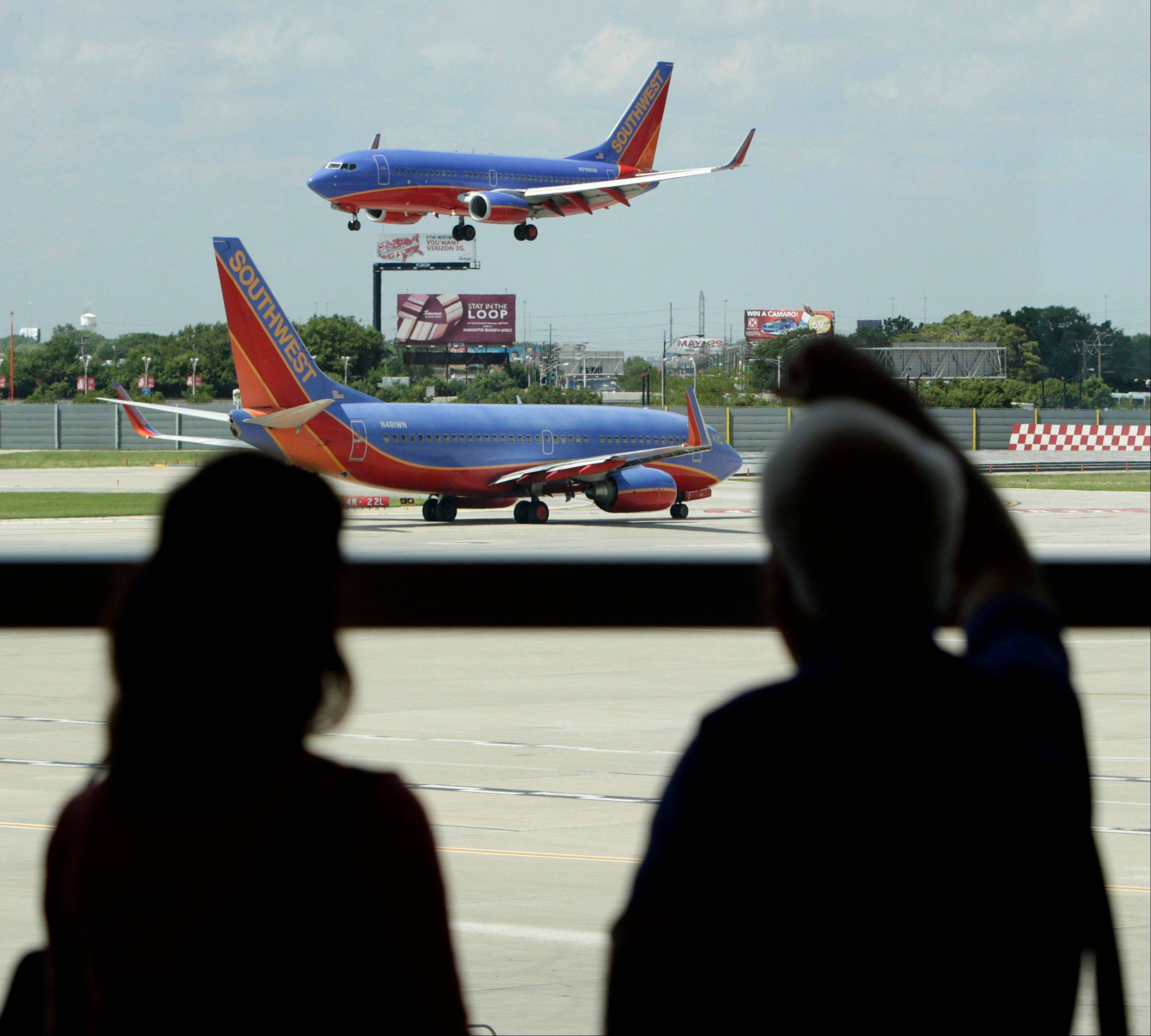 Southwest Airlines passengers watch as one plane waits to takeoff and another lands at Midway International Airport in Chicago. Mayor Rahm Emanuel has decided not to move forward with plans to lease Midway International Airport.