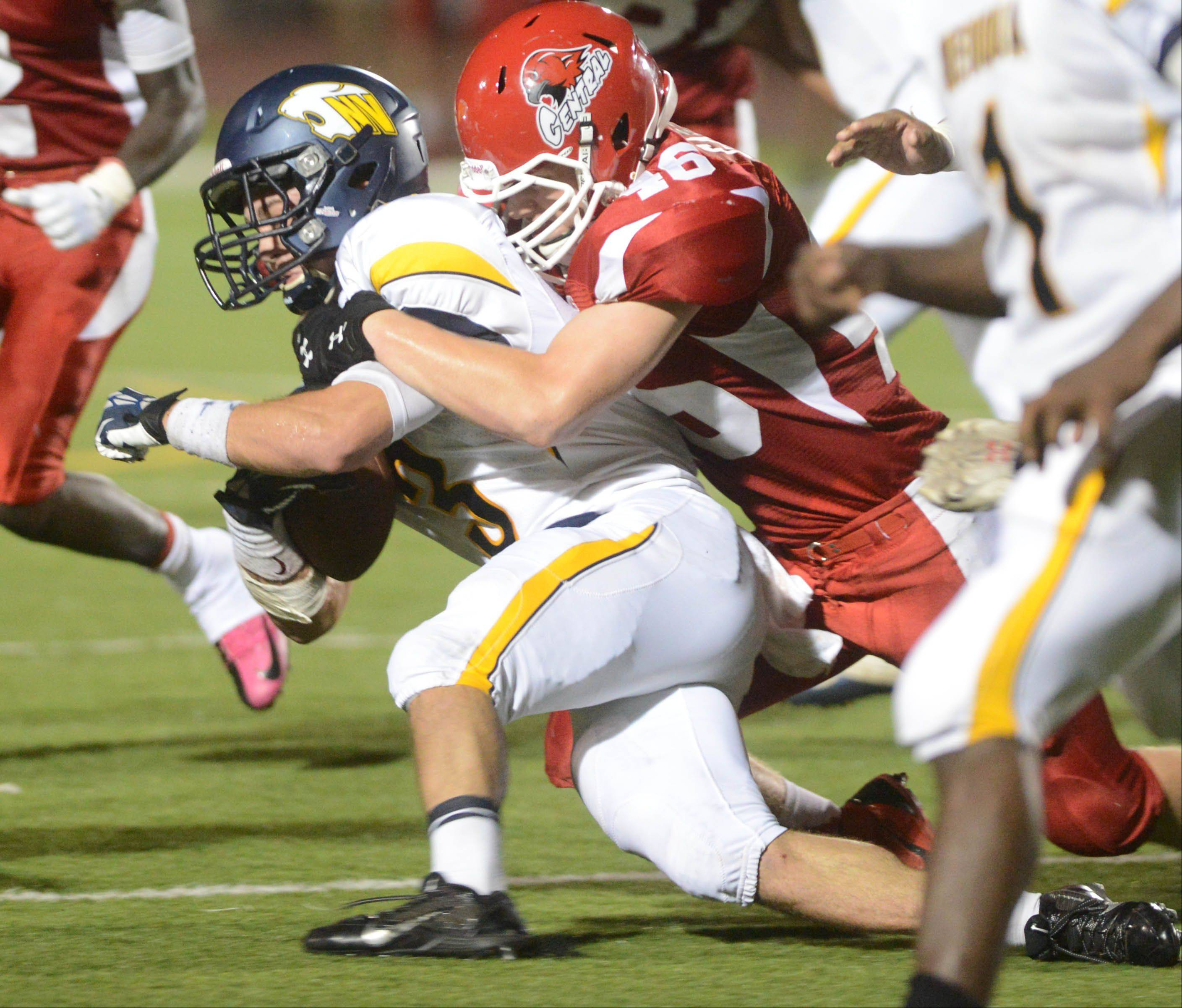 Mikey Dudek, left, of Neuqua Valley is pulled down by Billy Gammon of Naperville Central Friday in Naperville.