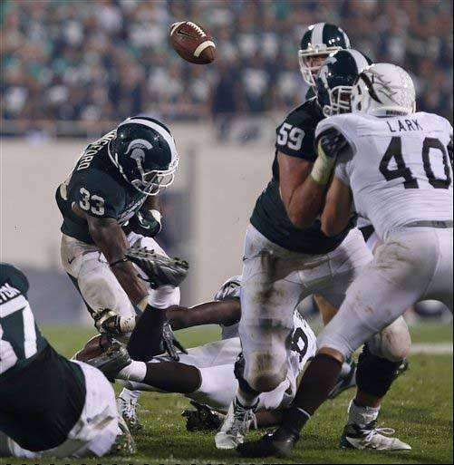 Michigan State�s Jeremy Langford (33) fumbles as he is hit by Western Michigan�s Rontavious Atkins during the third quarter of last week�s game in East Lansing, Mich.