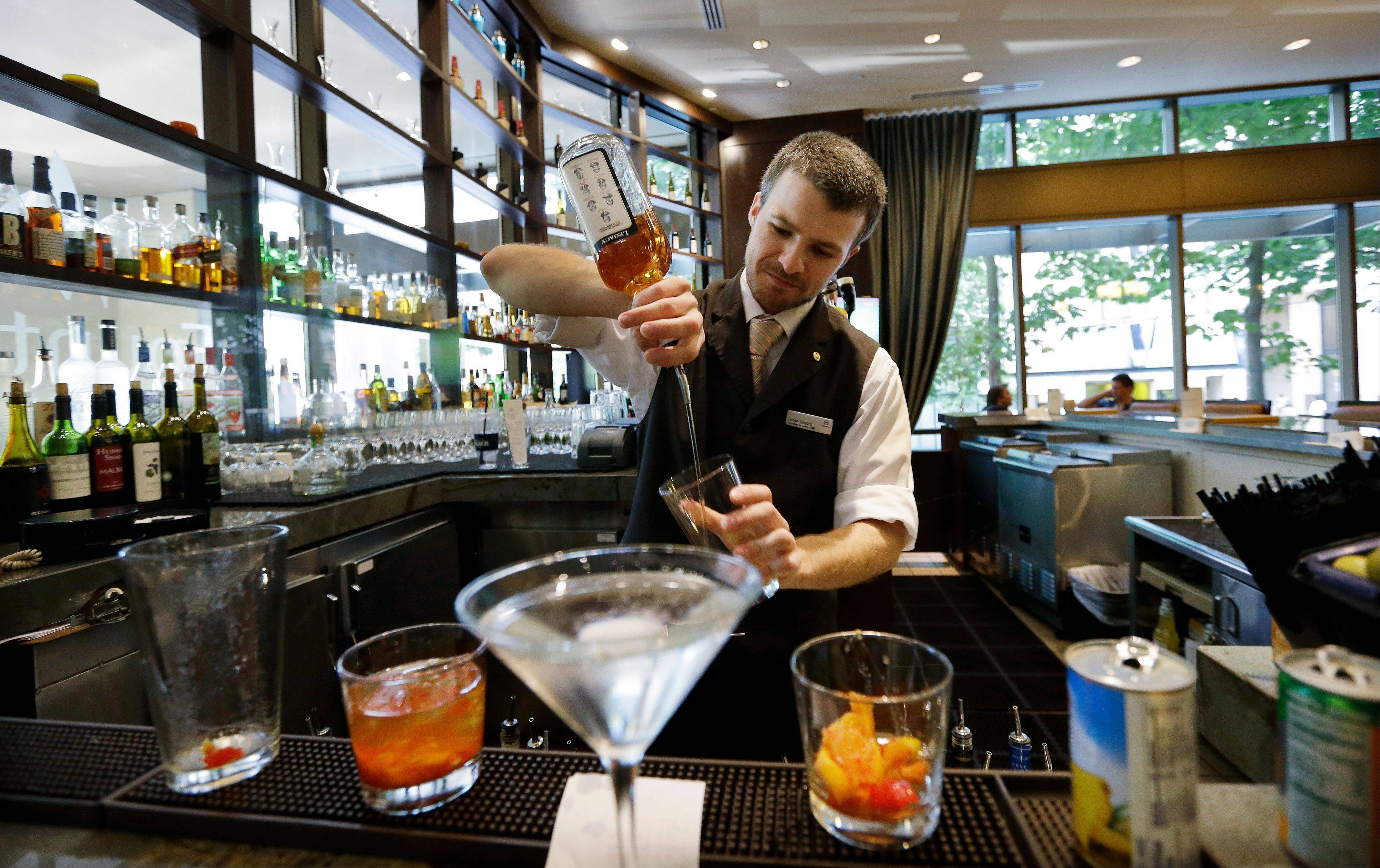"Bartender Derek Simoes mixes drinks in the newly redesigned bar during ""social hour"" at a Sheraton hotel in Seattle."