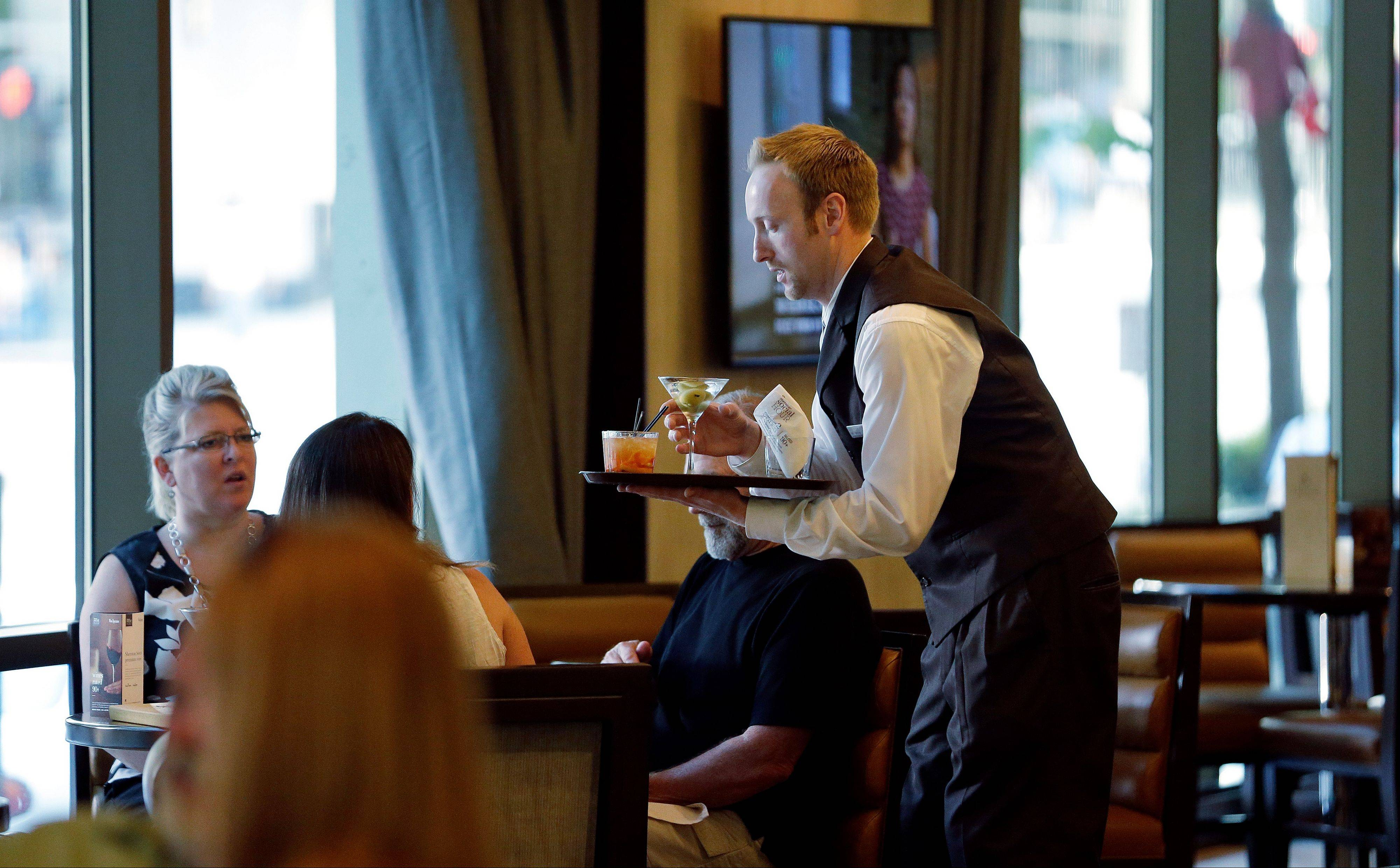 "A server brings drinks to guests in the newly redesigned bar during ""social hour"" at a Sheraton hotel in Seattle. Long treated as dead spaces that hotel guests raced through on the way to the elevator, lobbies are being transformed into places to work, surf the Web or meet friends for a drink."