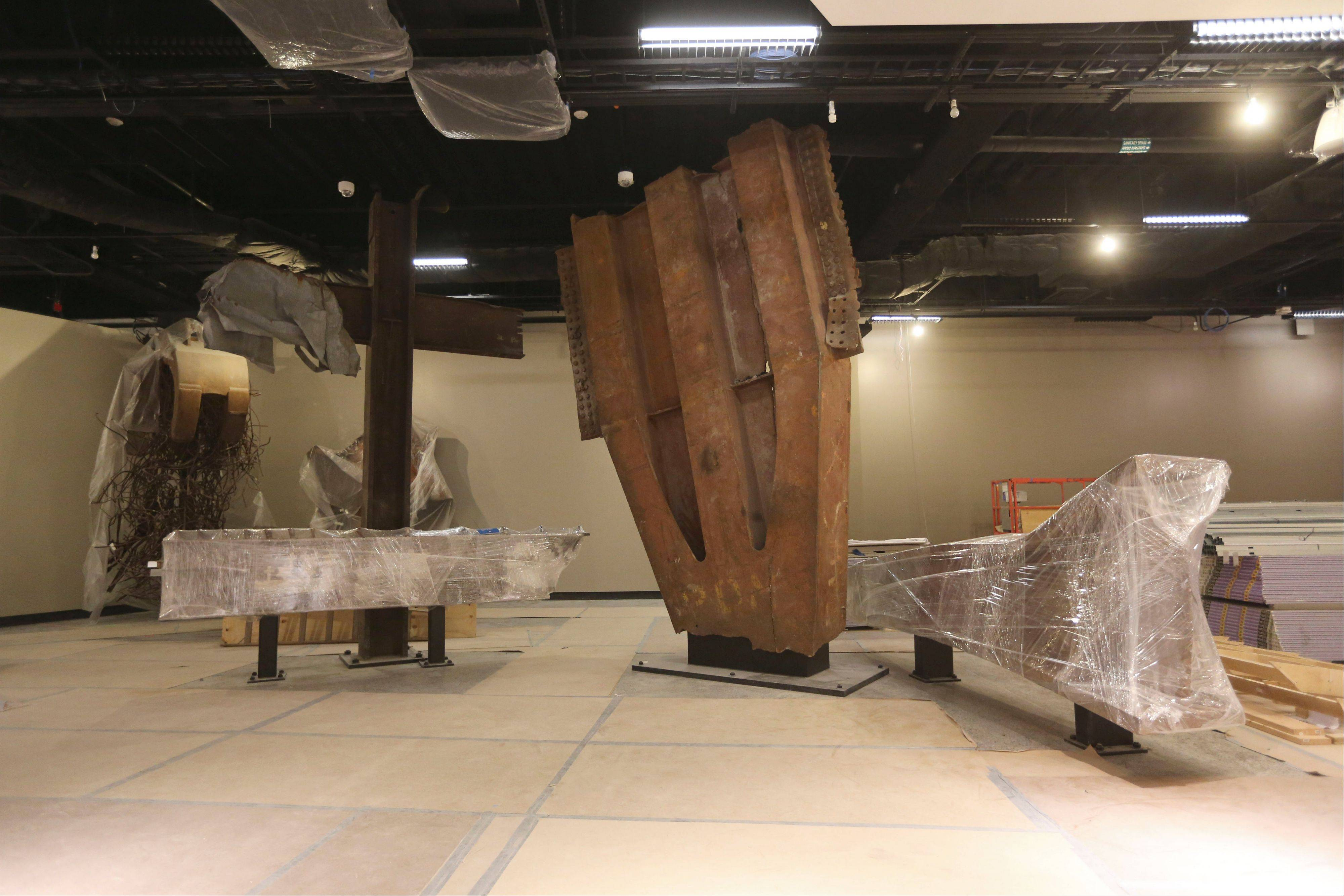 The 'Cross', left, intersecting steel beams found in the rubble of 6 World Trade Center and a fragment of a trident column, center, one of 84 that formed the exterior structure of each tower are displayed during a media tour Friday of the National September 11 Memorial and Museum.