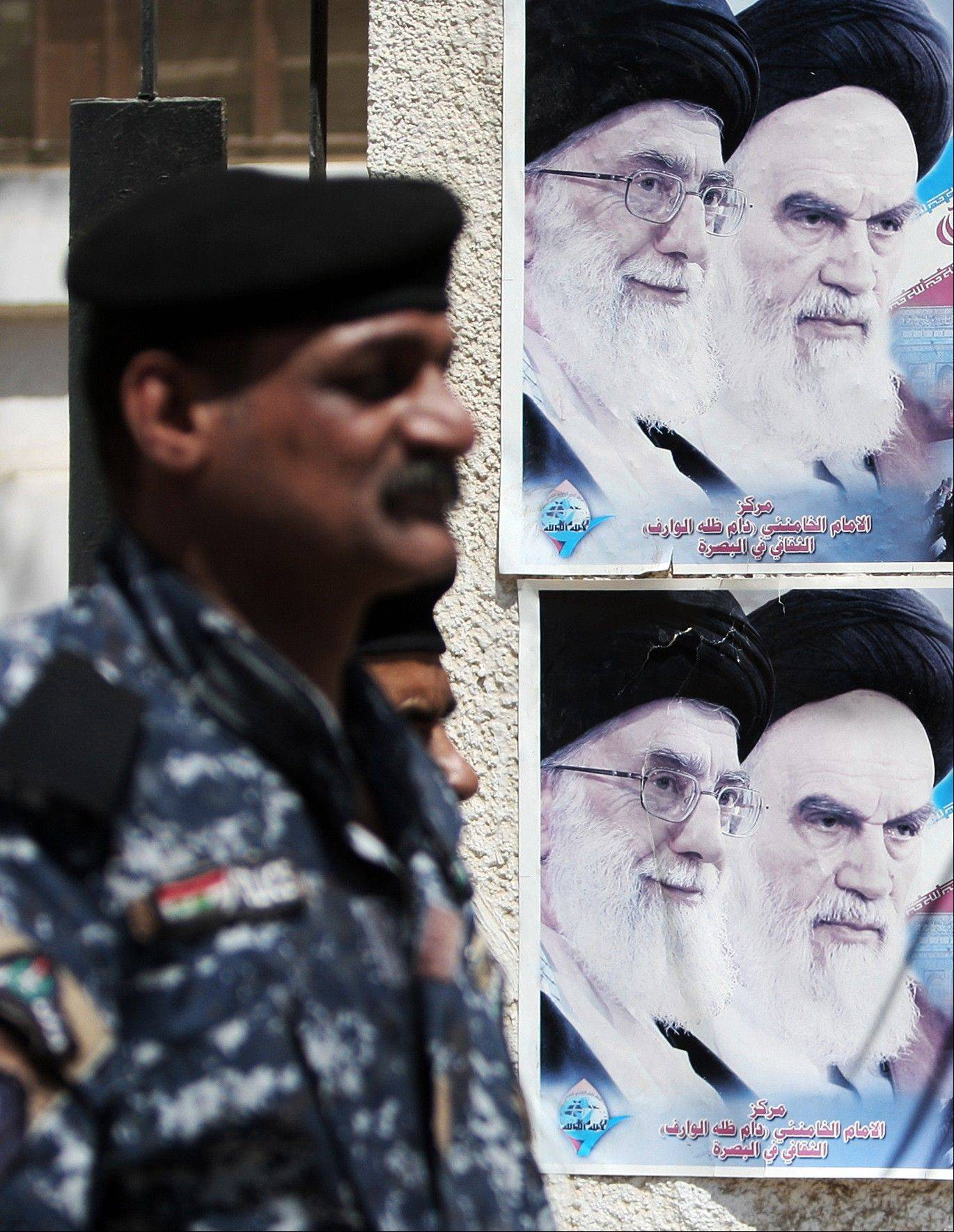 An Iraqi soldier stands guard next to a poster depicting late Iran's spiritual leaders Ayatollah Khomeini, right, and Ayatollah Khamenei, left, in Basra, 340 miles southeast of Baghdad, Iraq.