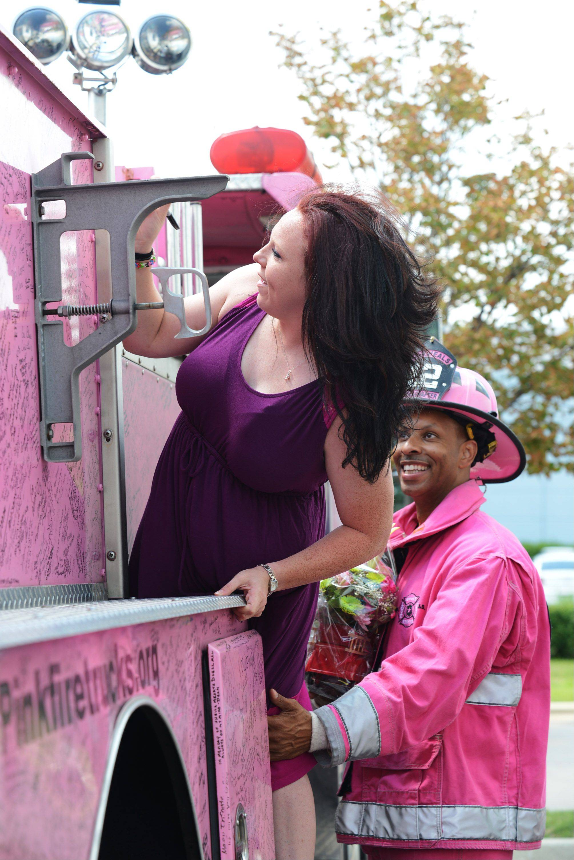Rebekah Gillette climbs one of the Pink Heals fire trucks in order to find an open space for her signature during the group's visit to Elgin in early August. Firefighter Chuck Goins waits nearby with a helpful hand. The nationwide breast cancer awareness group stopped at the Spring Hill Gymnastics in West Dundee in support of some of their employees who have and are fighting cancer.