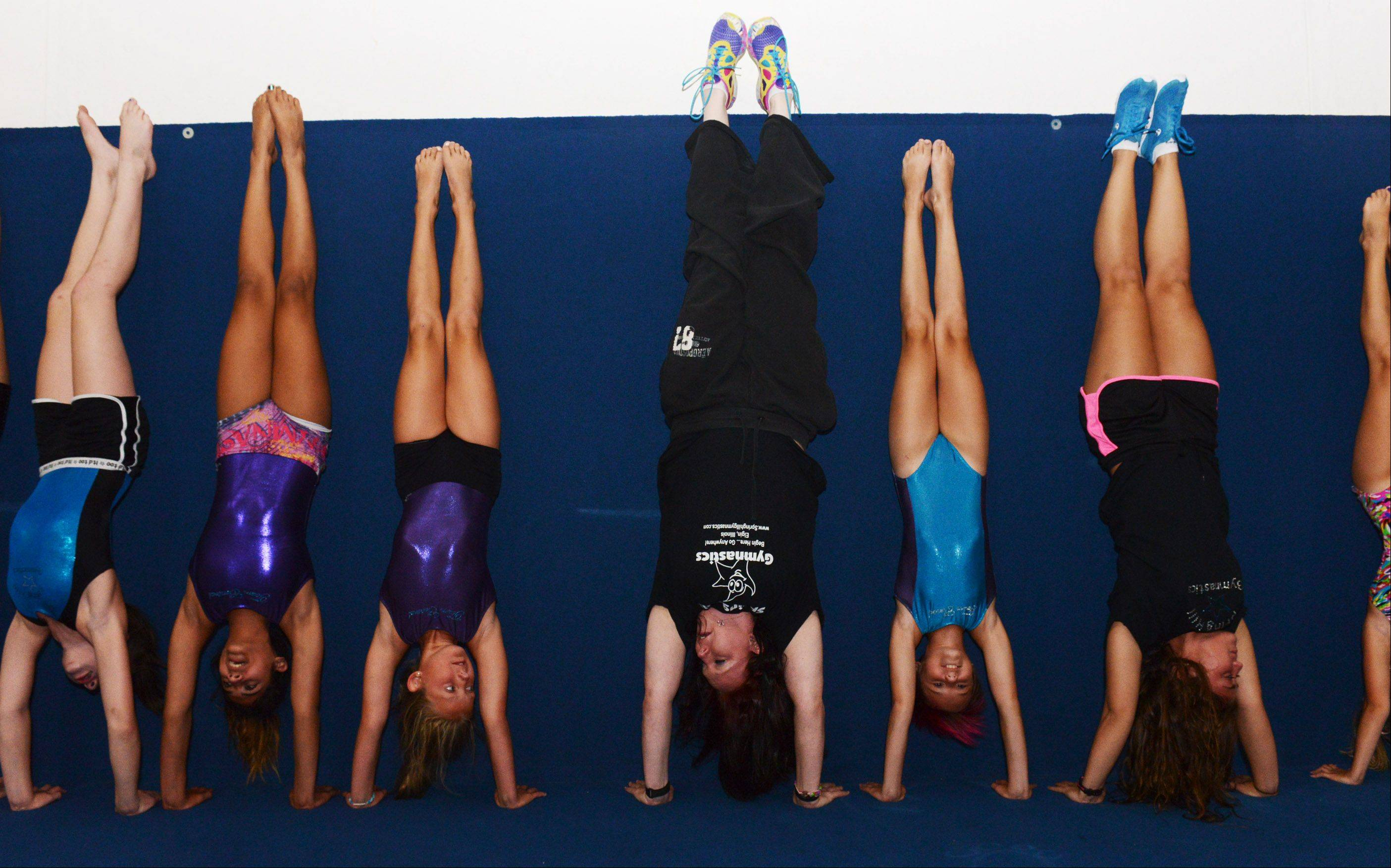 Rebekah Gillette leads the Greater Illinois Junior Olympics team in handstands at Spring Hill Gymnastics in Elgin.