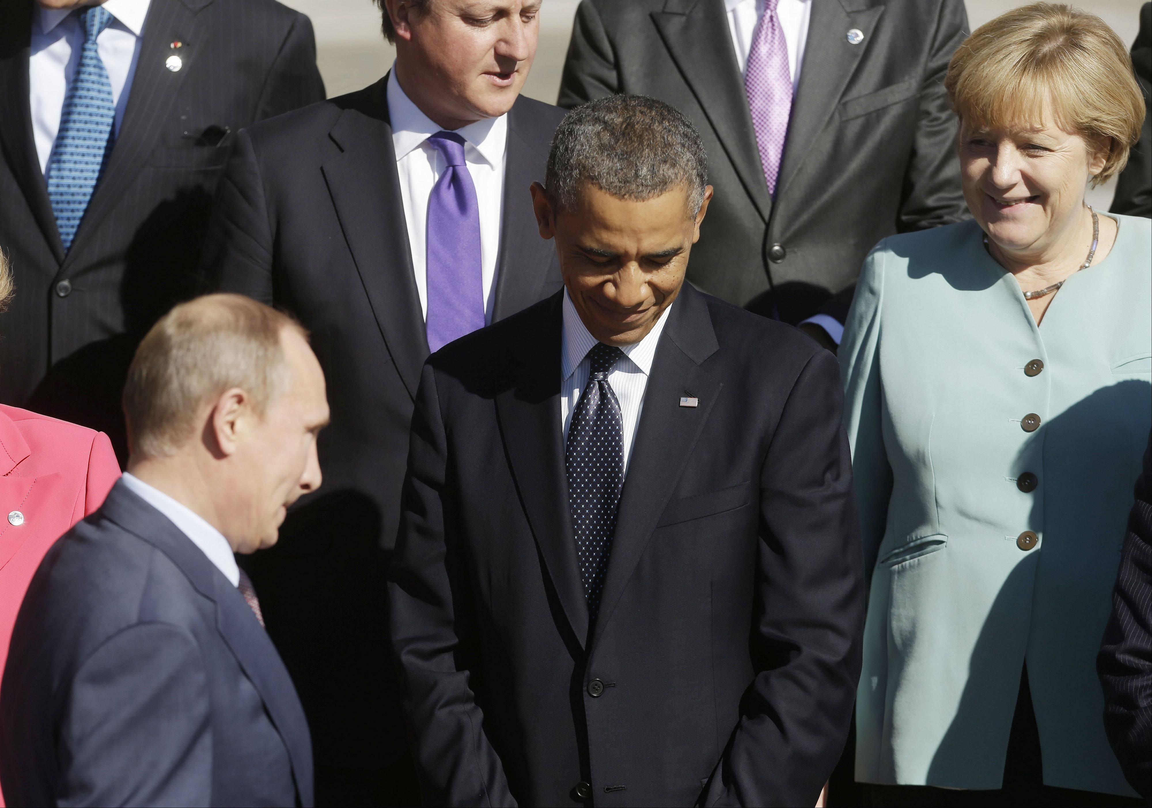 Russia's President Vladimir Putin, left, walks past U.S. President Barack Obama to join with other leaders for a photo at the G-20 summit at the Konstantin Palace in St. Petersburg, Russia, Friday.