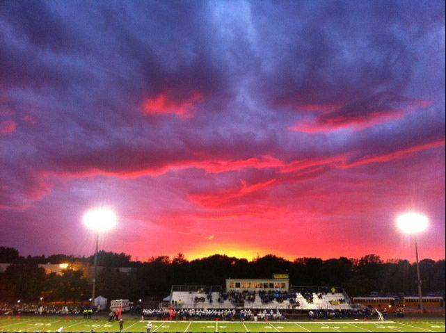 A beautiful sunset spreads across the skies over a football game at Stevenson High School in Lincolnshire on September 21, 2012 as the Stevenson Patriots play against the Warren Blue Devils.