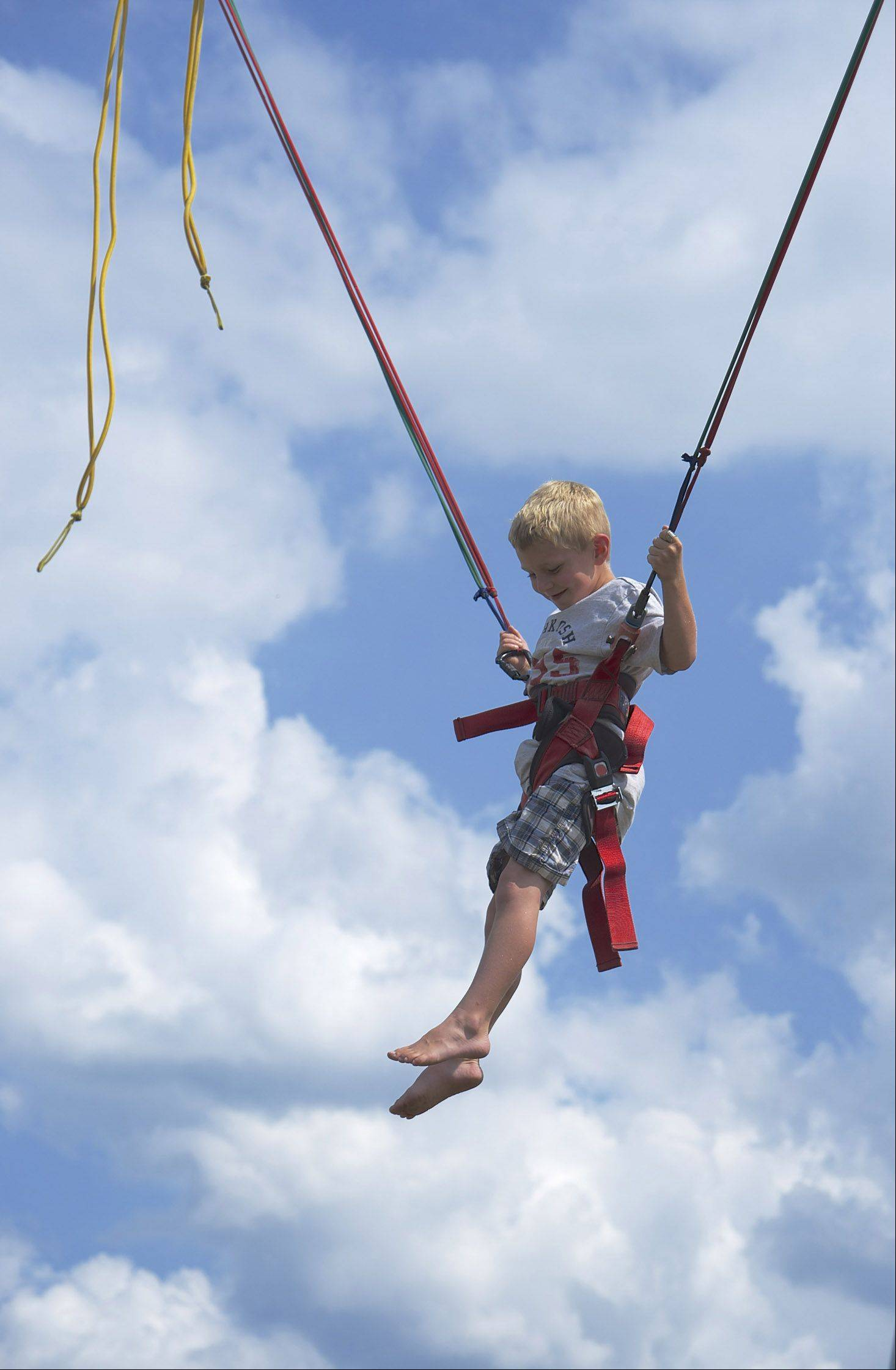At the Kenosha County Fair, a young boy is all smiles after he takes a challenge and tries bungee jumping.