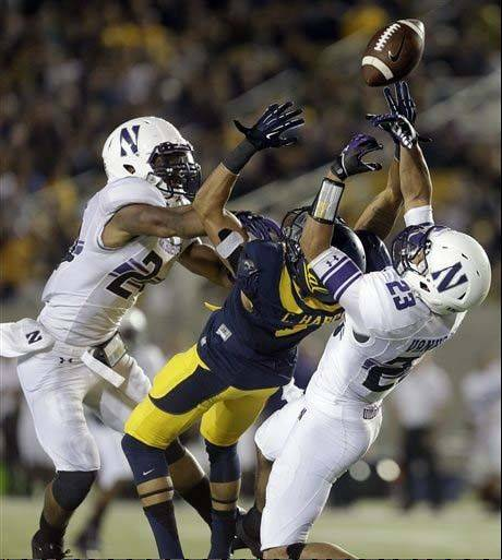 Northwestern's Ibraheim Campbell, left, and Nick VanHoose prevent California's Chris Harper from making the catch in last Saturday's season opener.