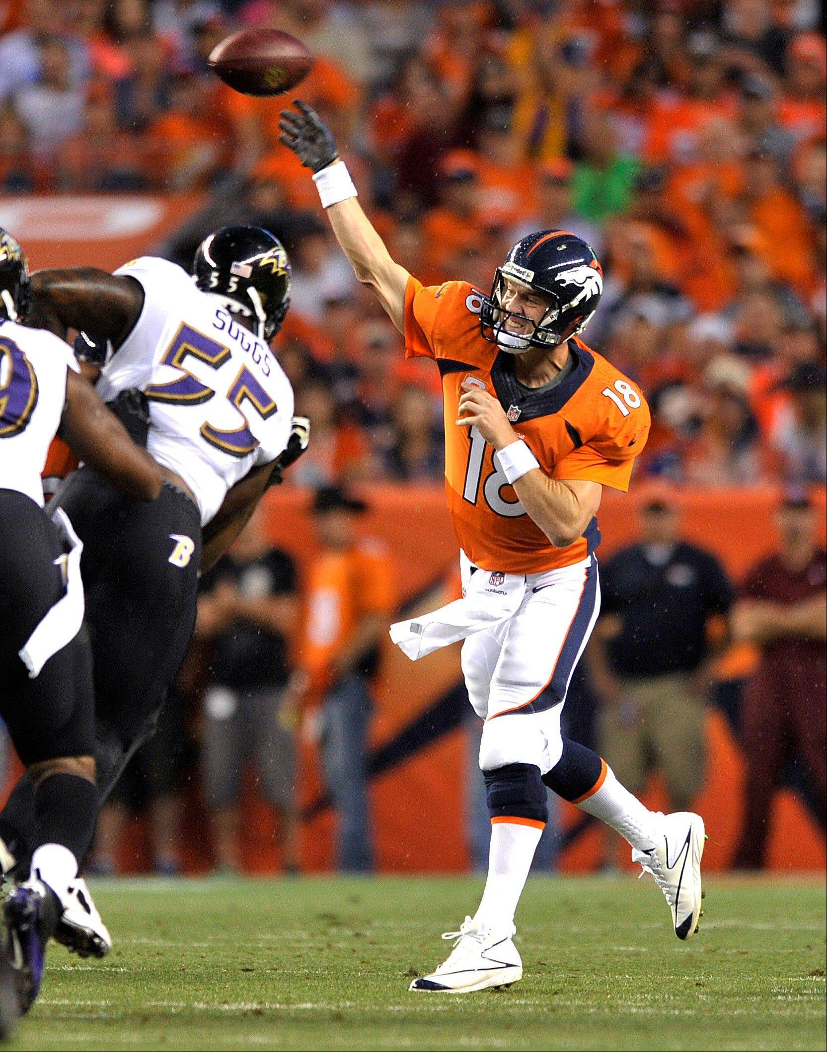 Denver Broncos quarterback Peyton Manning (18) throws under pressure from Baltimore Ravens outside linebacker Terrell Suggs (55) during the first half of an NFL football game, Thursday, Sept. 5, 2013, in Denver.