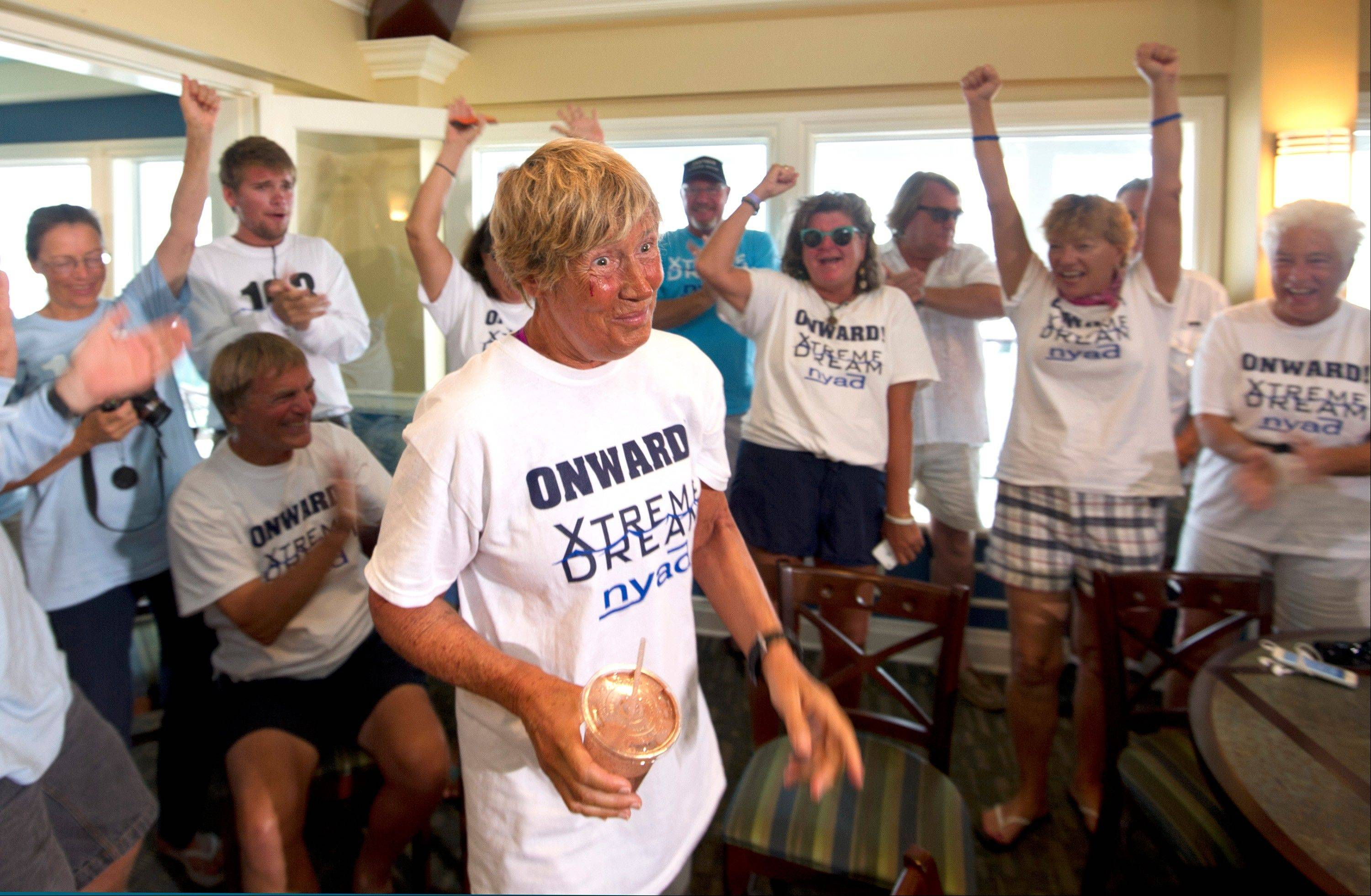 In this photo provided by the Florida Keys News Bureau, endurance swimmer Diana Nyad is cheered by her crew just before beginning a news conference Tuesday in Key West, Fla. Nyad, 64, is the first swimmer to cross the Florida Straits without the security of a shark cage.