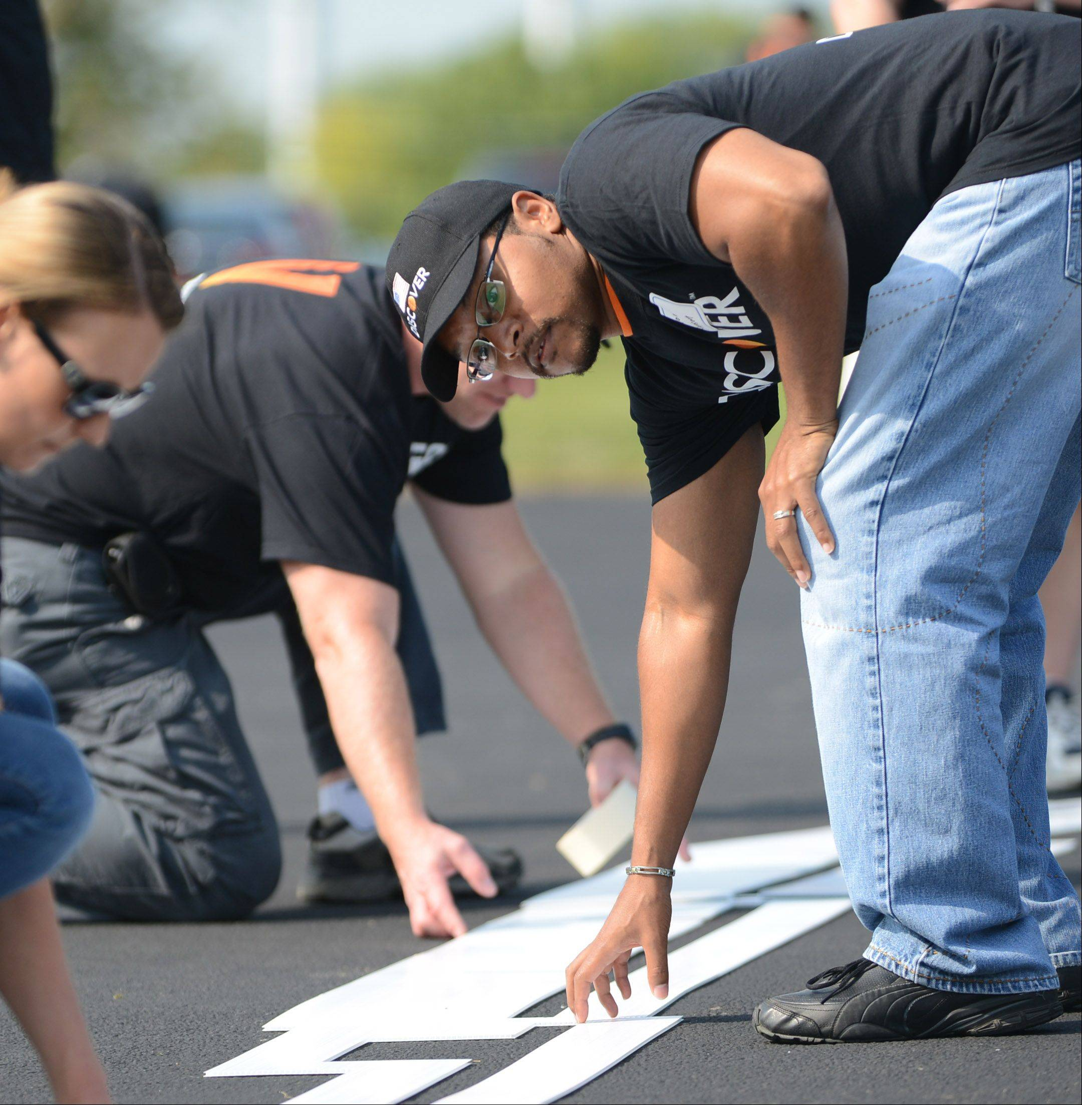 Jason Simpson, of Bartlett, helps line up a template before the lines can be painted on the basketball court.