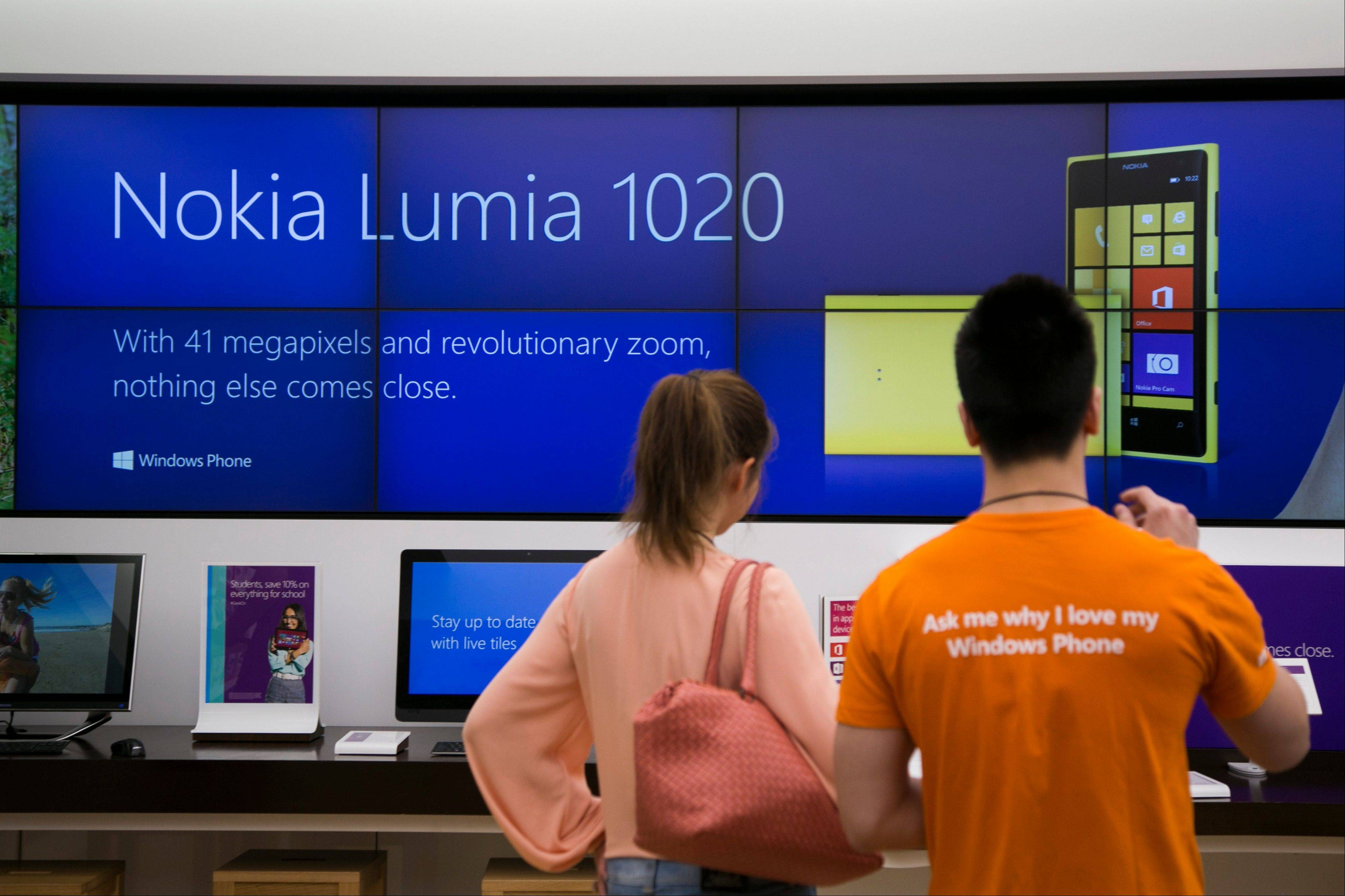 Sales associate Jacky Hom, right, assists customer Katie Guo with a product demo of the Nokia Oyj Lumia 1020 mobile device at a Microsoft Corp. store in Boston.