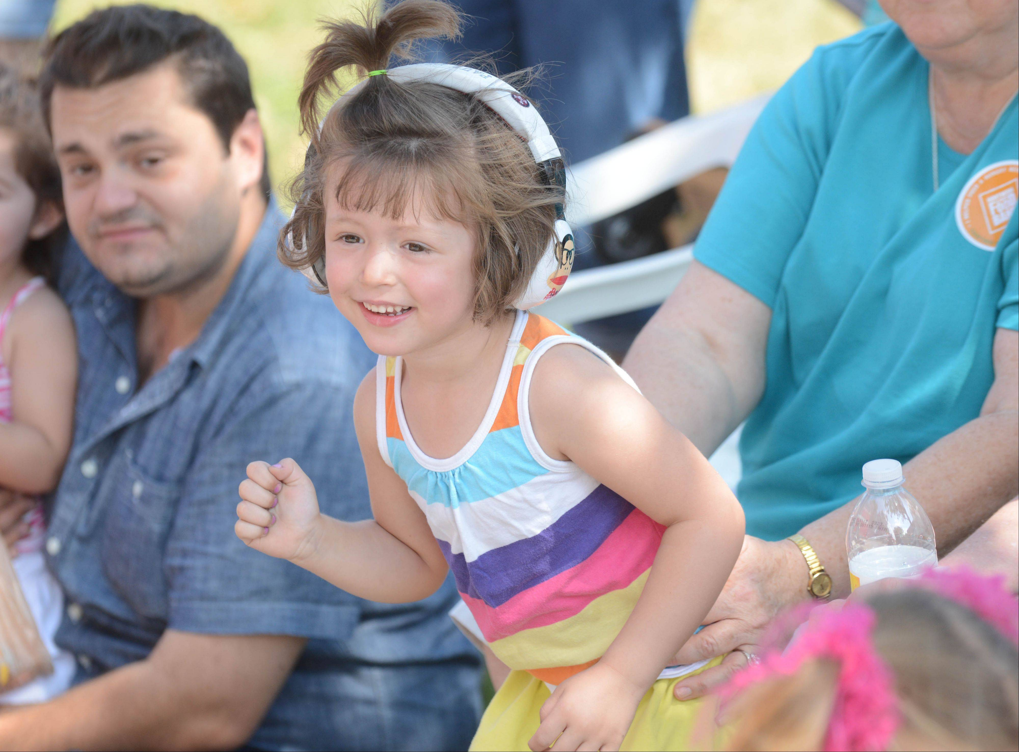 Paige Franzen, 3, of Chicago pumps her fist so the fire trucks will blow their horn Saturday during Bloomingdale�s Septemberfest at Old Town Park. The fest included a parade and booths with local food vendors and services.