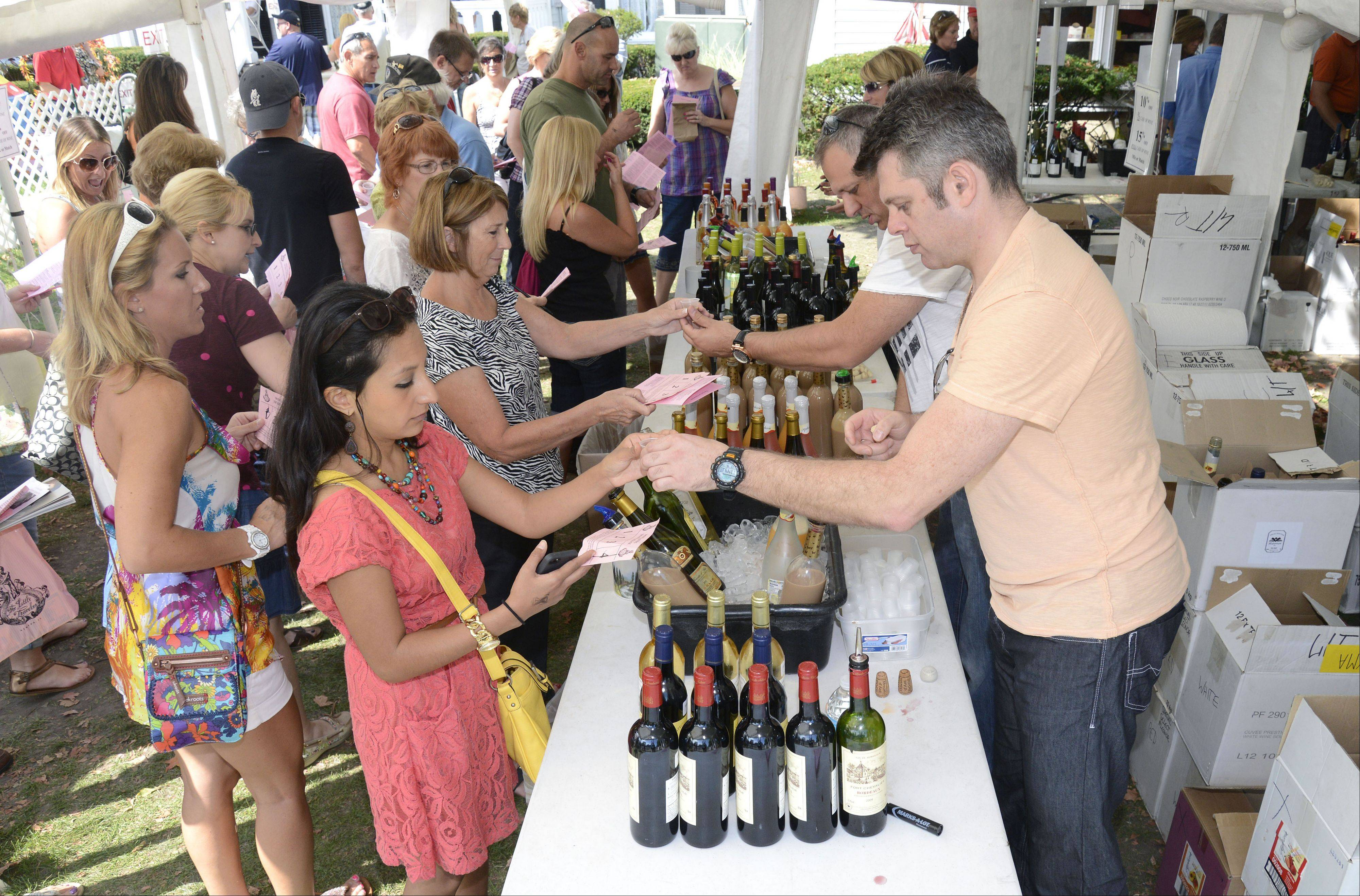 Liz Krahn of LaGrange is served a sample by Sergey Beylis with VMA Group Inc. wine and spirit distributors out of Elk Grove Village on Saturday at the Festival of the Vine in Geneva.