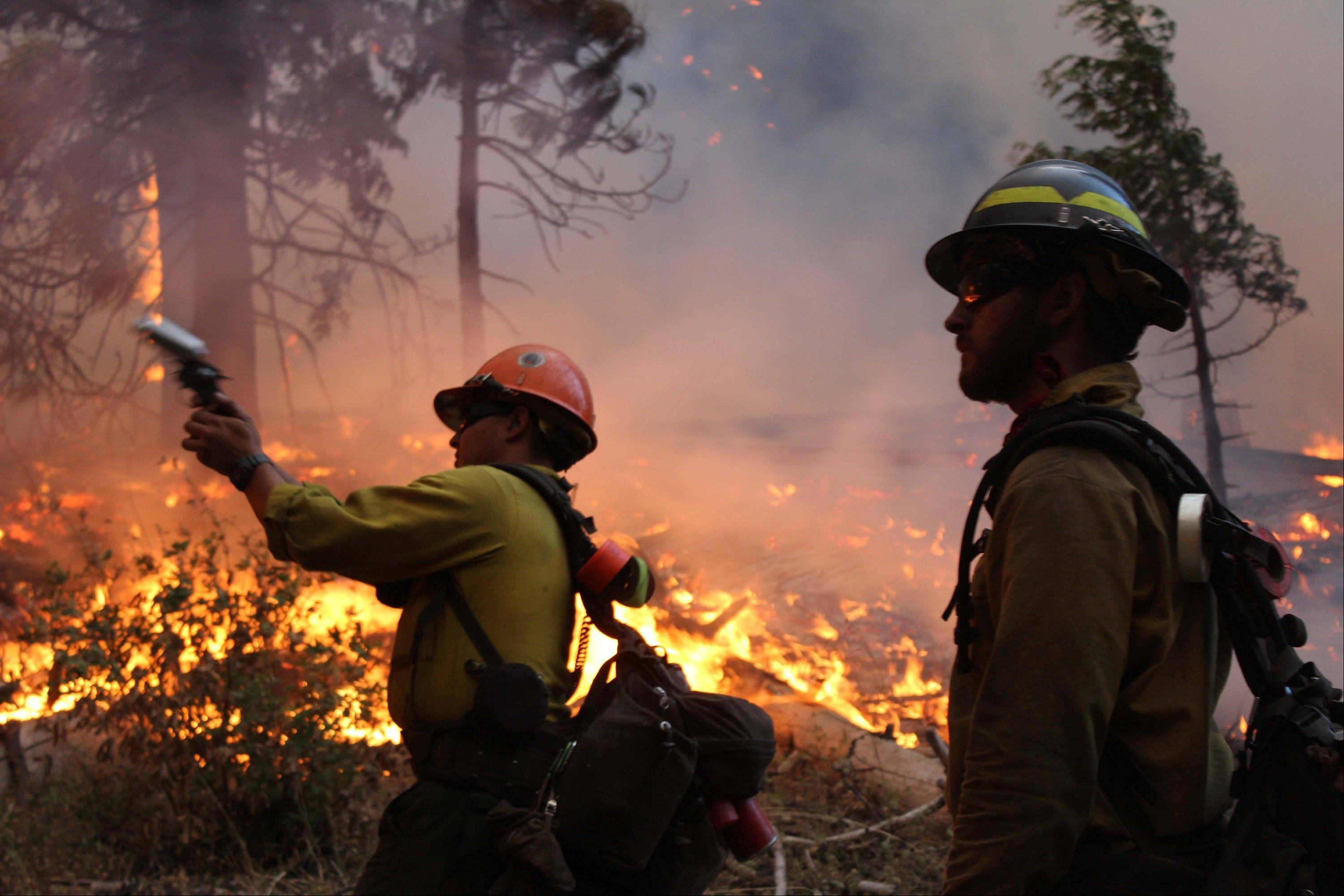 Associated Press/U.S. Forest Service Fire crew members stand watch near a controlled burn operation as they fight the Rim Fire Monday near Yosemite National Park in California.