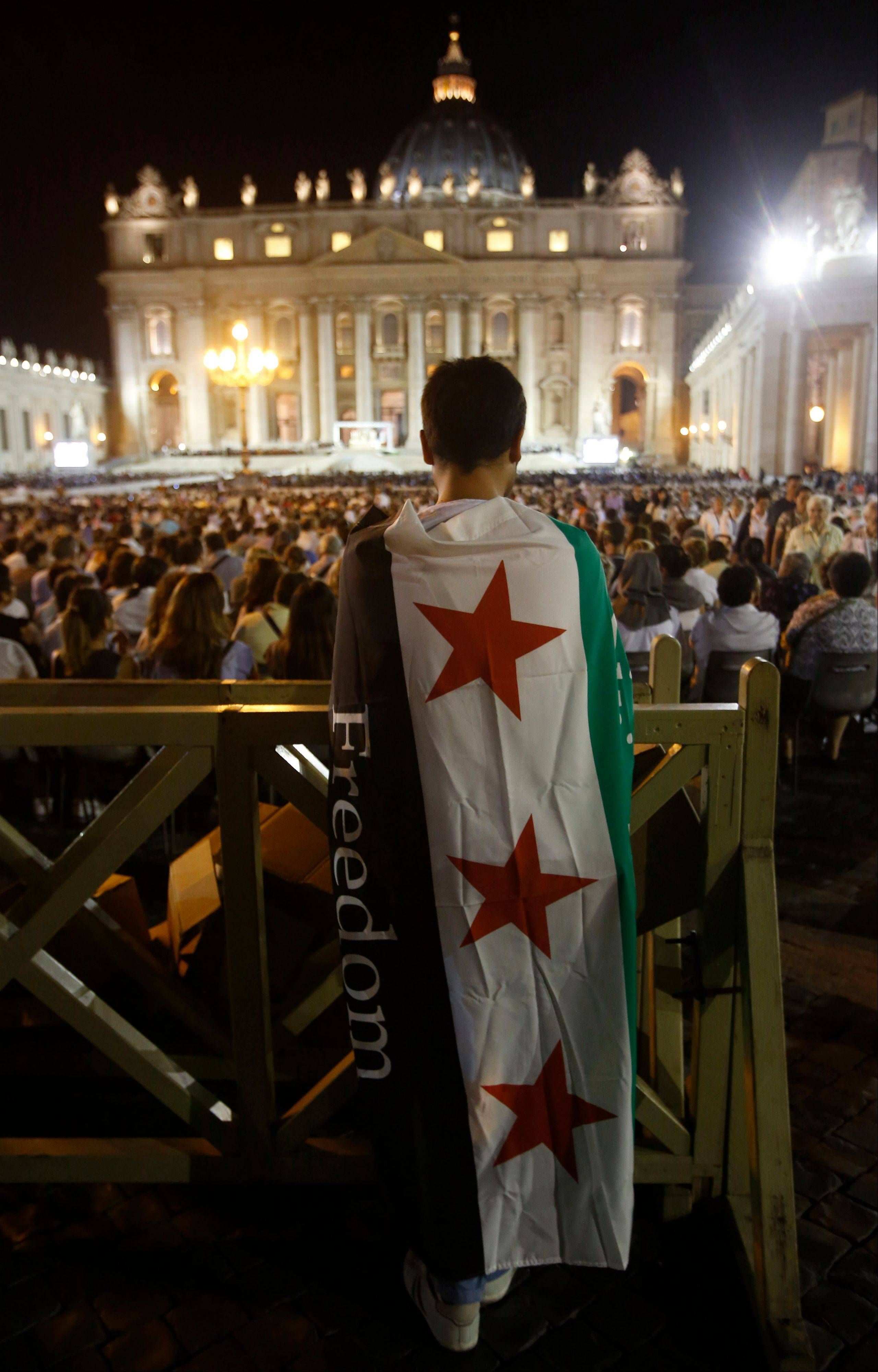 A man wearing a Syrian flag prays Saturday during a vigil for peace attended by Pope Francis in St. Peter�s Square at the Vatican.