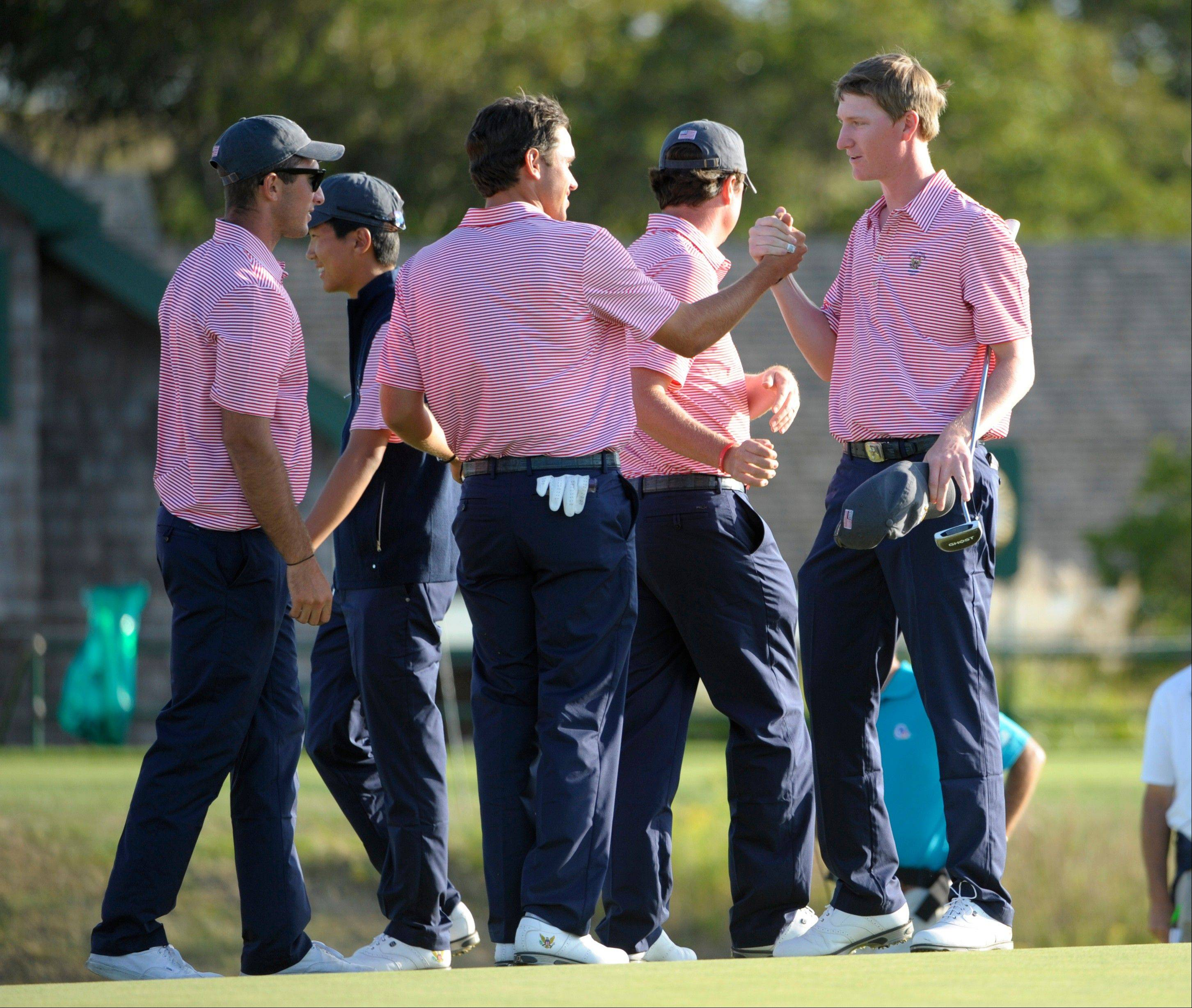 Jordan Niebrugge, right, is greeted by U.S. teammates Max Homa, left, and Cory Whitsett after Niebrugge completed the 18th hole Saturday in the Walker Cup tournament in Southampton, N.Y.