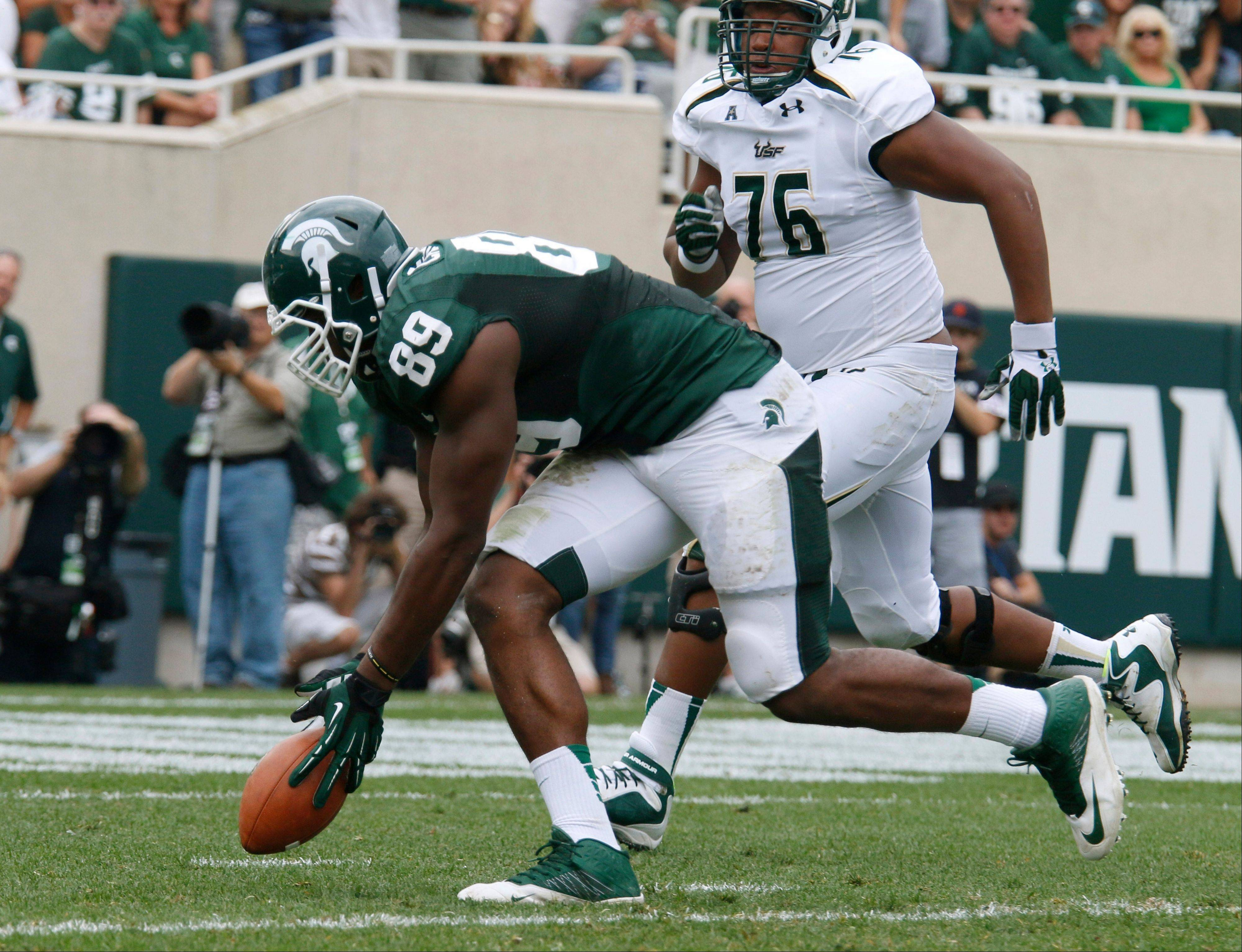 Michigan State�s Shilique Calhoun picks up a fumble and returns it for a touchdown in front of South Florida�s Darrell Williams during the second quarter Saturday in East Lansing, Mich.