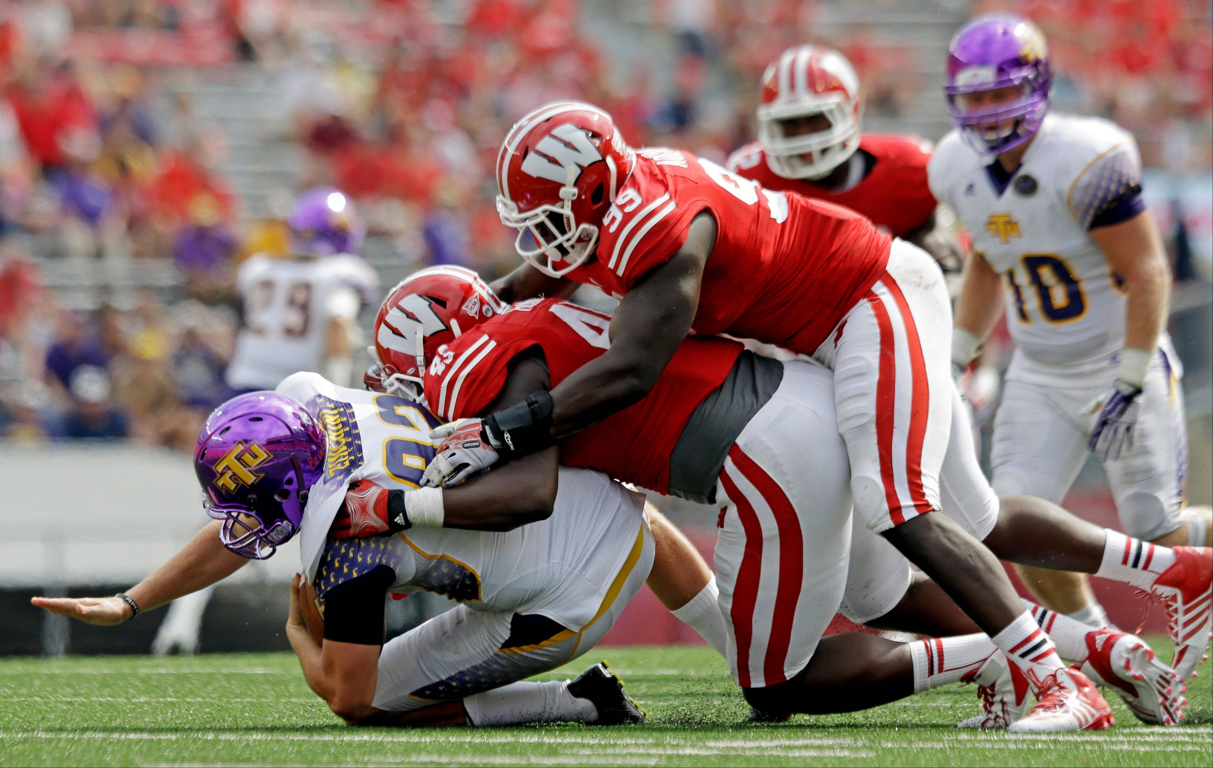 Wisconsin�s Warren Herring (45) and James Adeyanju (99) tackle Tennessee Tech punter Chad Zinchini during the second half of Saturday�s game in Madison.