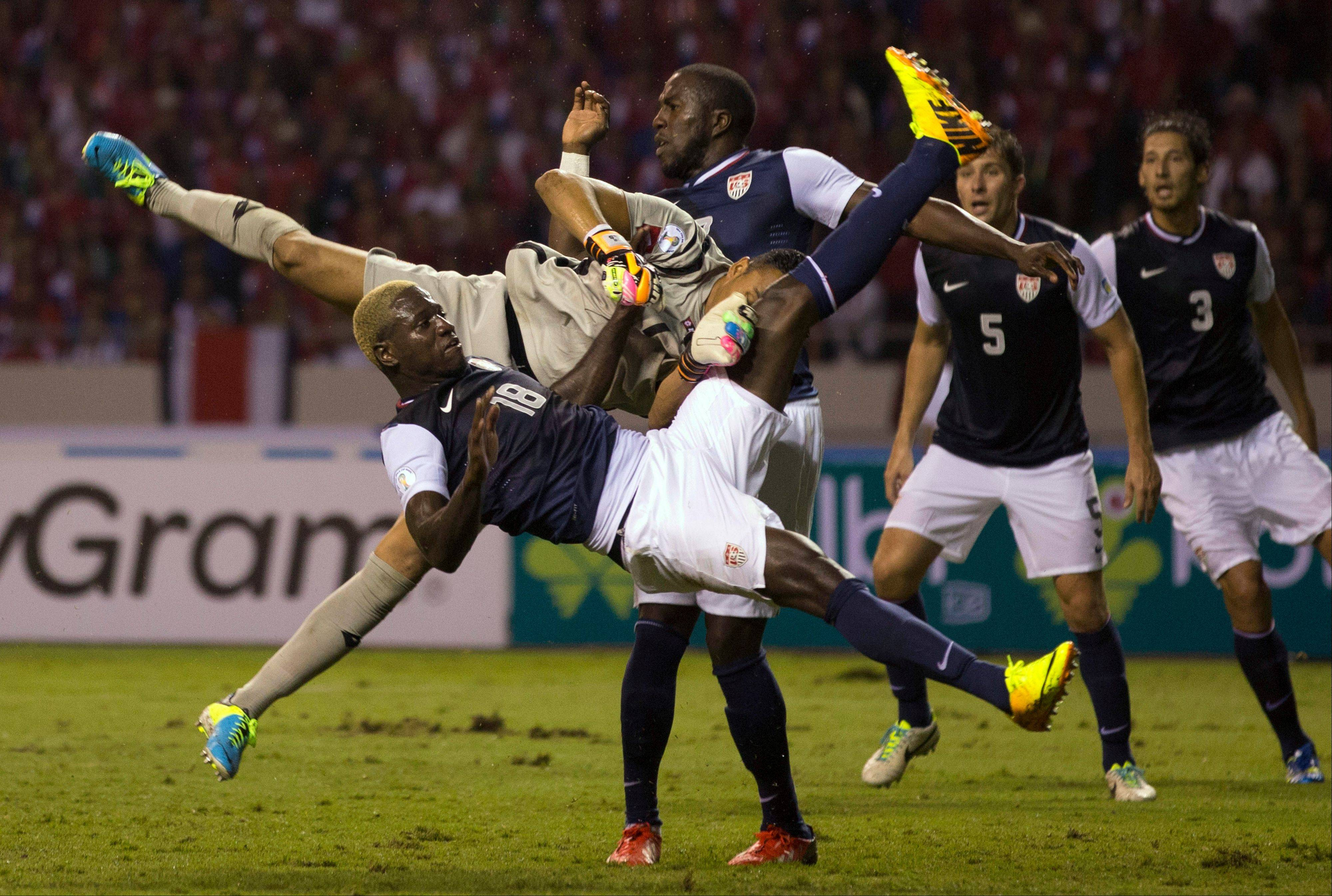 The United States� Eddie Johnson, front, collides with Costa Rica�s goalkeeper Keylor Navas, who blocked his attempt to score during a 2014 World Cup qualifier Friday in San Jose, Costa Rica. Behind at center is the United States� Jozy Altidore.