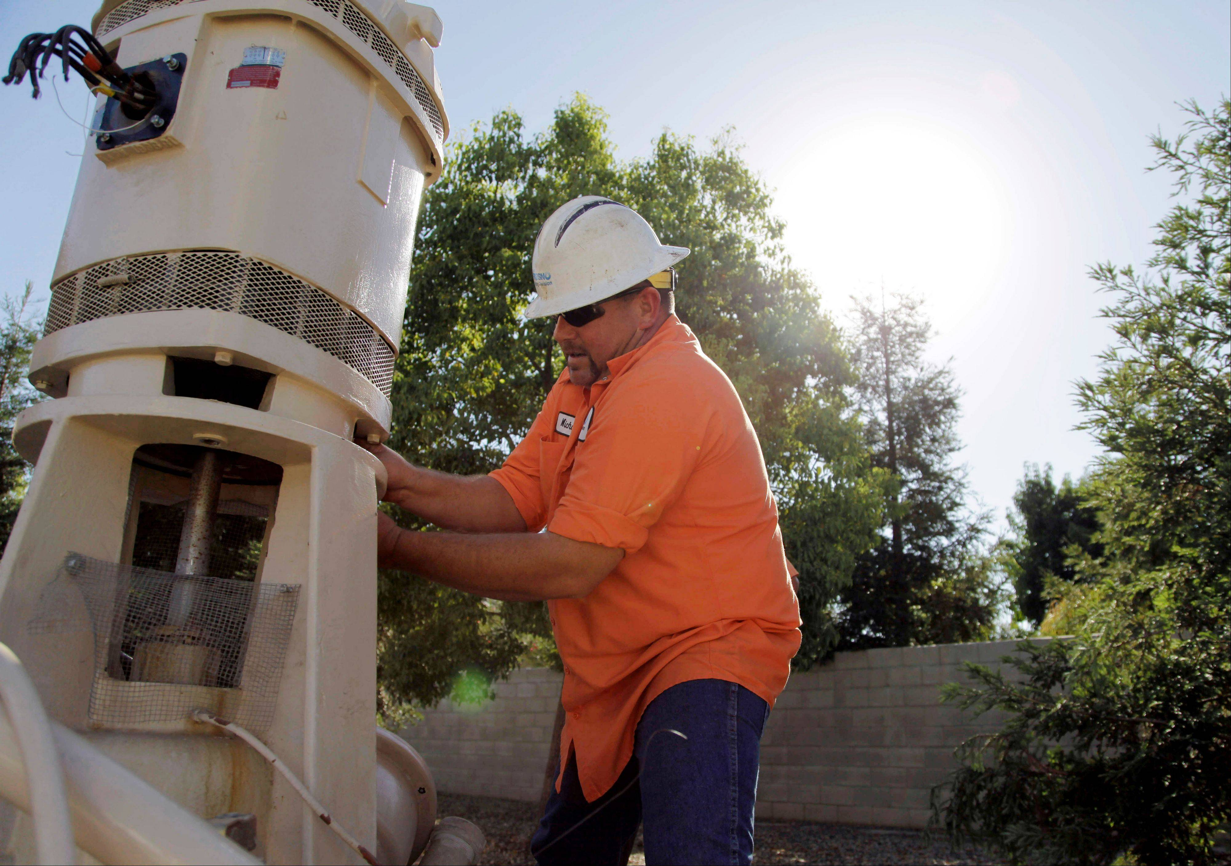 Micha Berry, with the city of Fresno's water division, unscrews the motor that sits on top of a groundwater well in order to repair the well's pump, in Fresno, Calif.