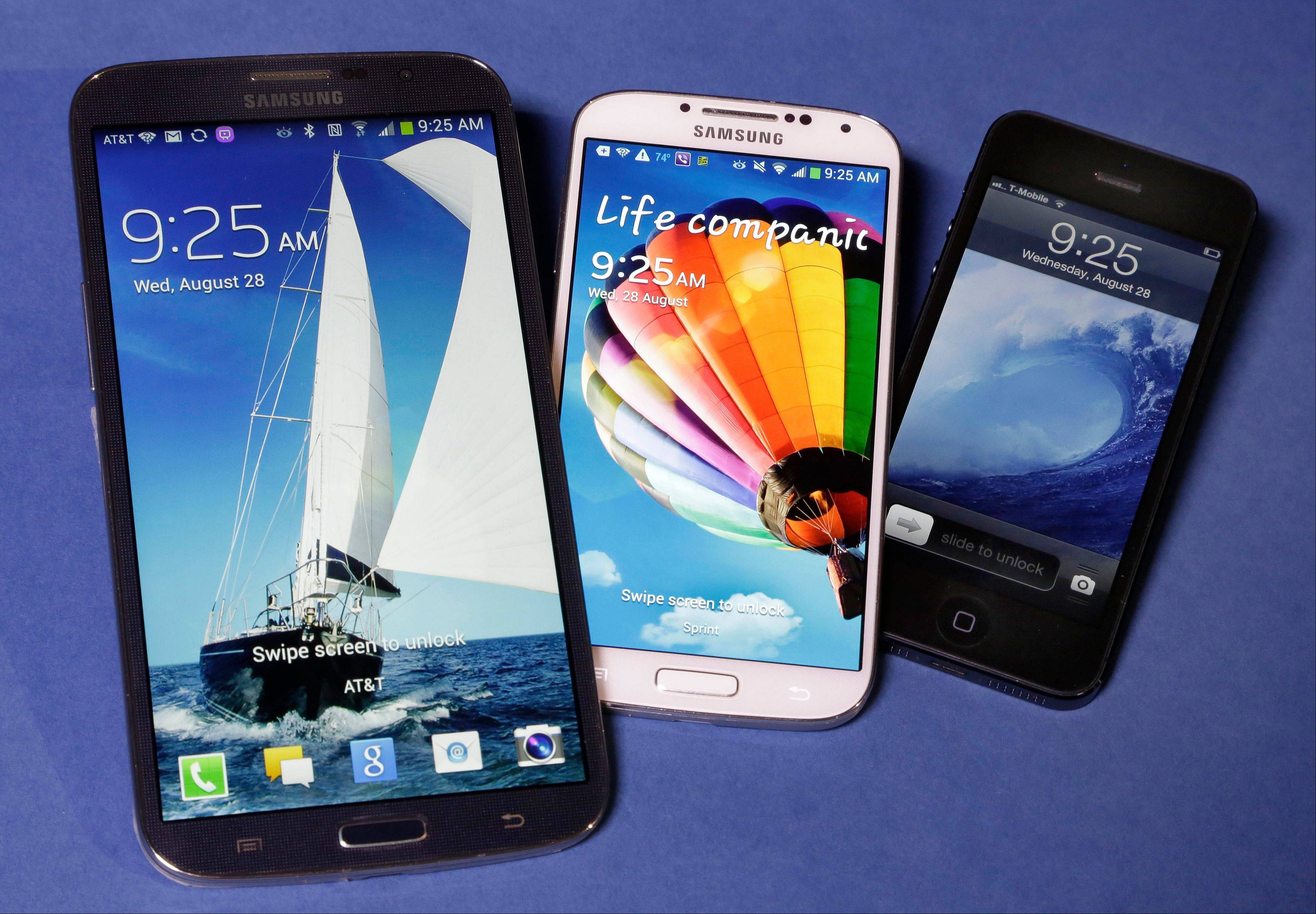 The Samsung Galaxy Mega, left, Samsung Galaxy S4, center, and Apple iPhone 5 are shown. With a screen measuring 6.3 inches diagonally, the Galaxy Mega is almost as big as a 7-inch tablet computer. The difference: It makes phone calls.